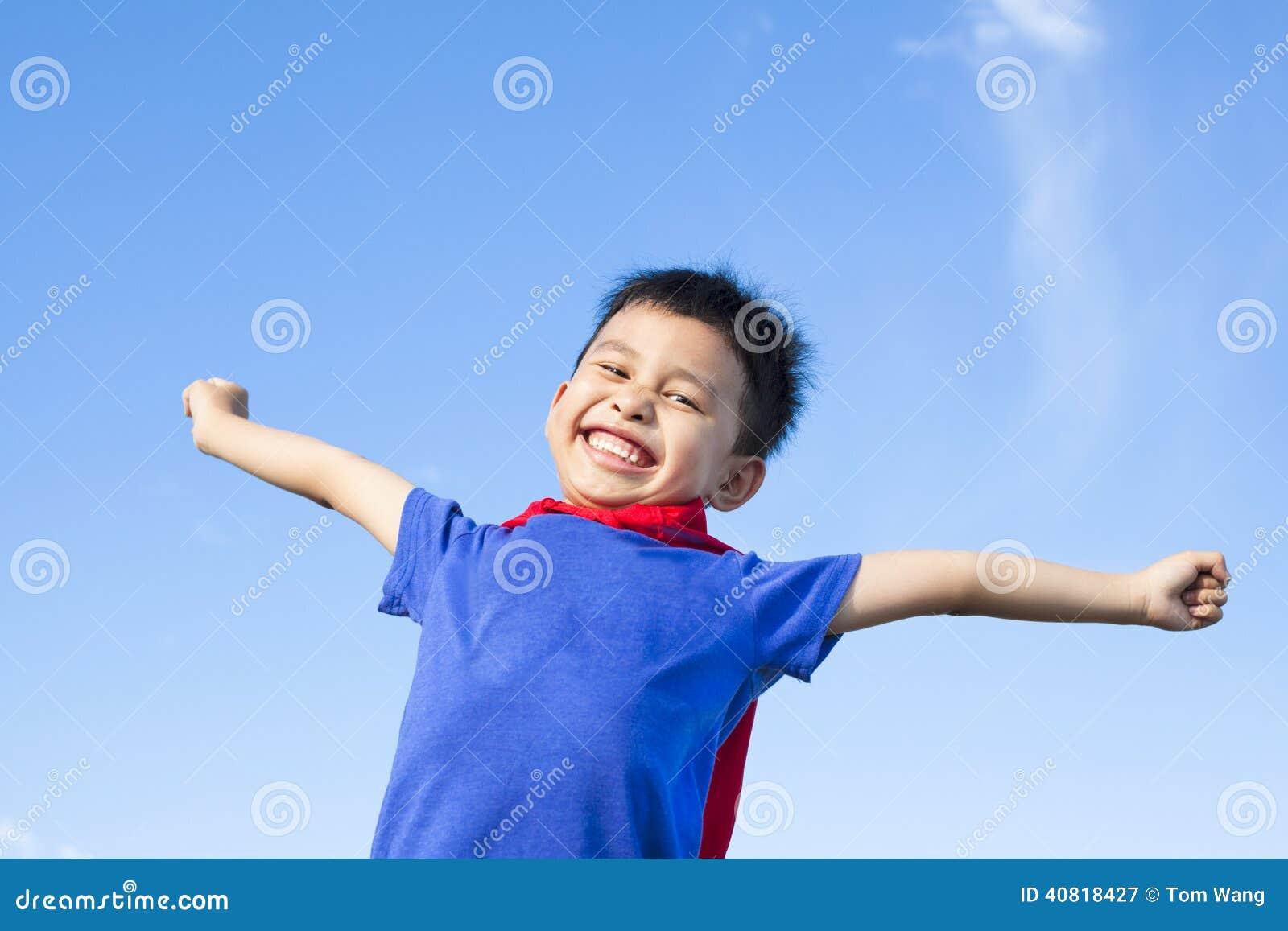O rapaz pequeno feliz imita o super-herói e abre os braços com céu azul