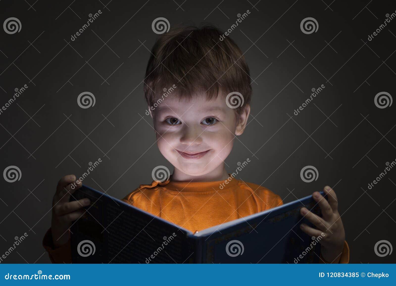 O rapaz pequeno feliz leu o livro no fundo preto