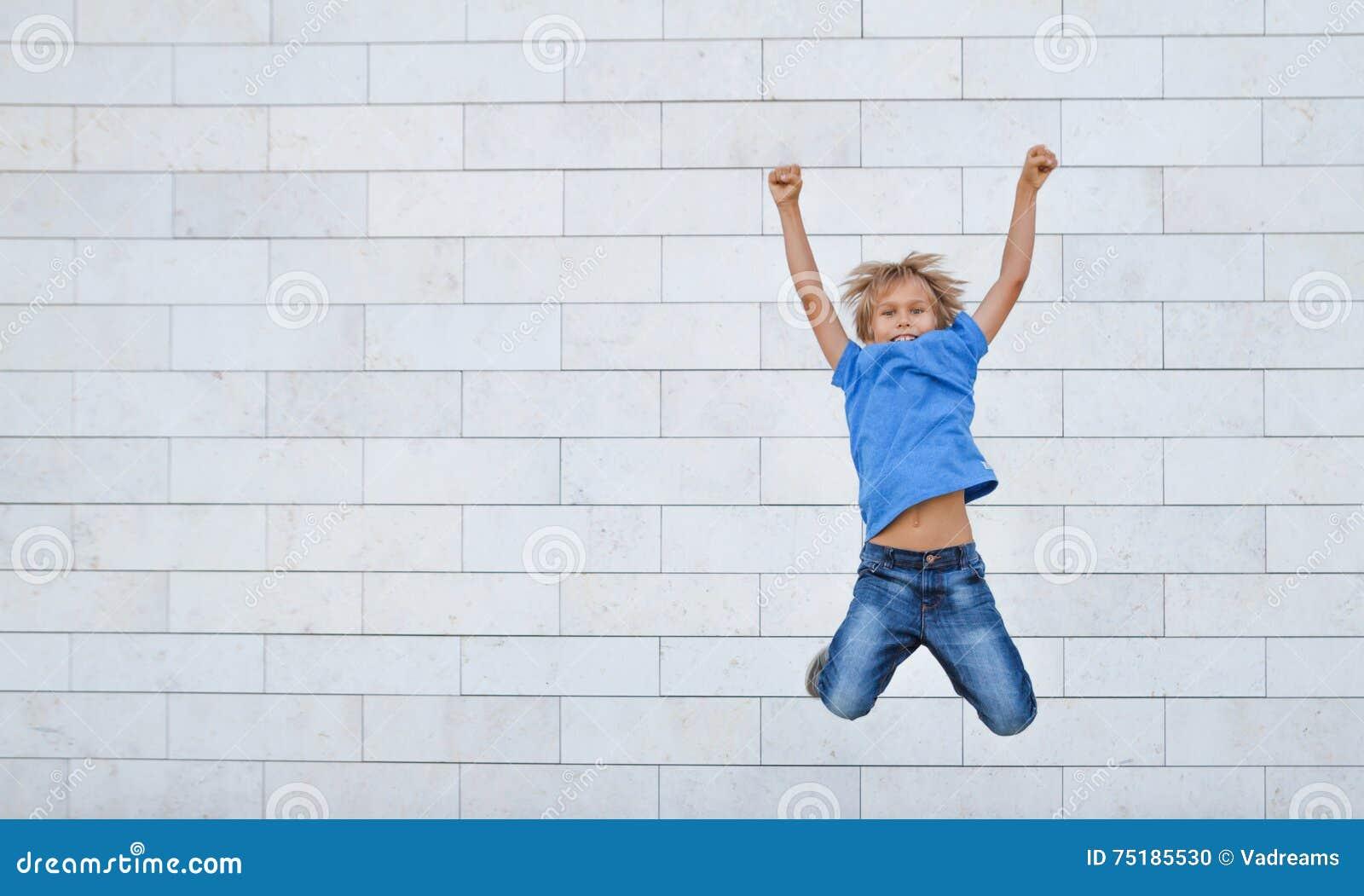 O rapaz pequeno feliz salta na elevação Povos, infância, felicidade, liberdade, conceito do movimento