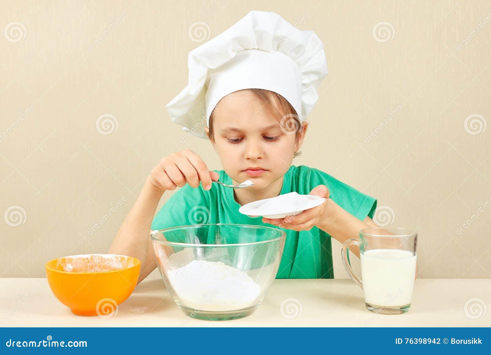 O rapaz pequeno no chapéu do cozinheiro chefe derrama o açúcar para o bolo de cozimento