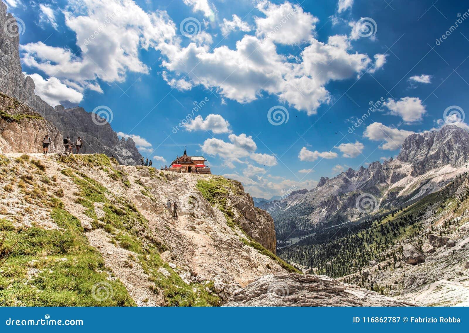 O refúgio e os trekkers de Preuss no pé do Vajolet elevam-se Como visto da fuga trekking do refúgio de Vajolet à passagem de Prin