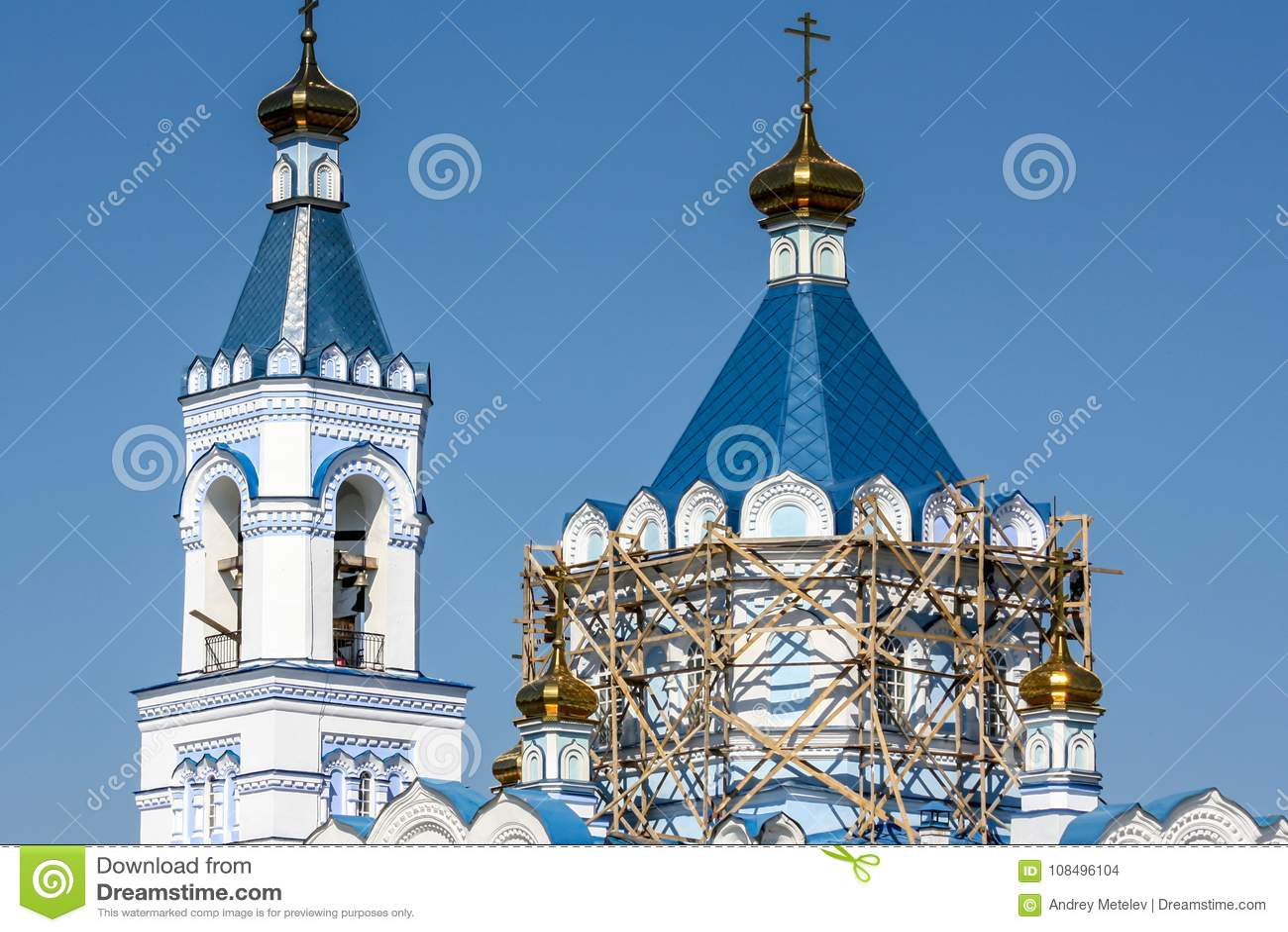 O reparo do andaime da igreja ortodoxa na torre, em um telhado azul e no céu azul