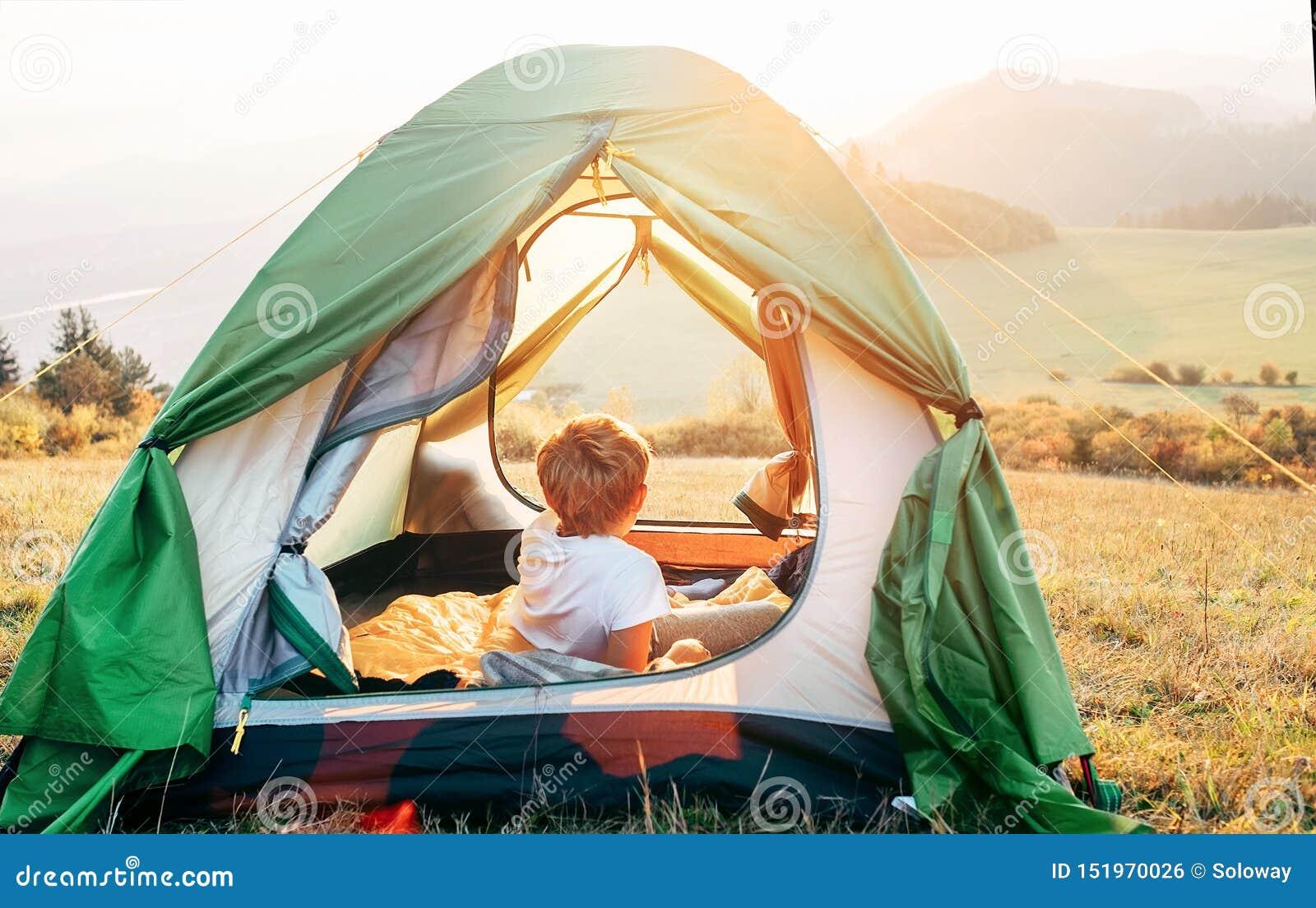 O resto do menino na barraca de acampamento e aprecia com luz do por do sol no vale da montanha