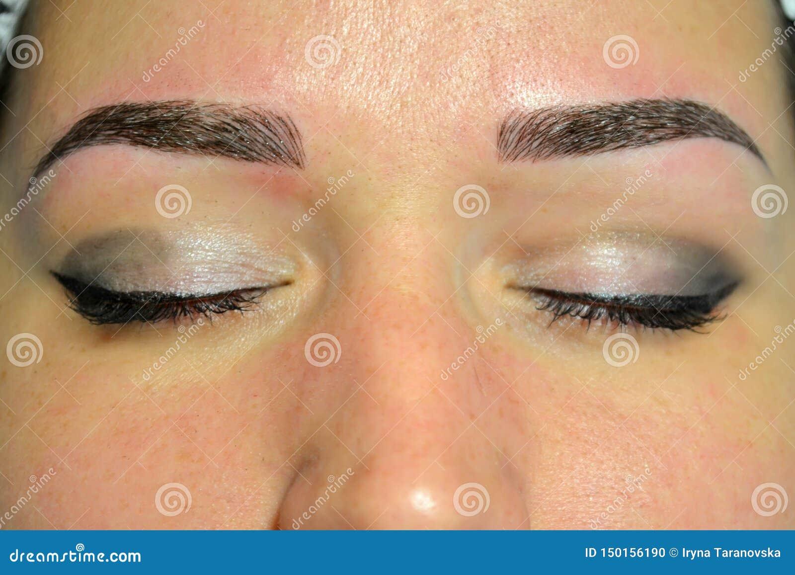 O resultado terminado de microblading, sobrancelhas escuras, composição permanente nas sobrancelhas