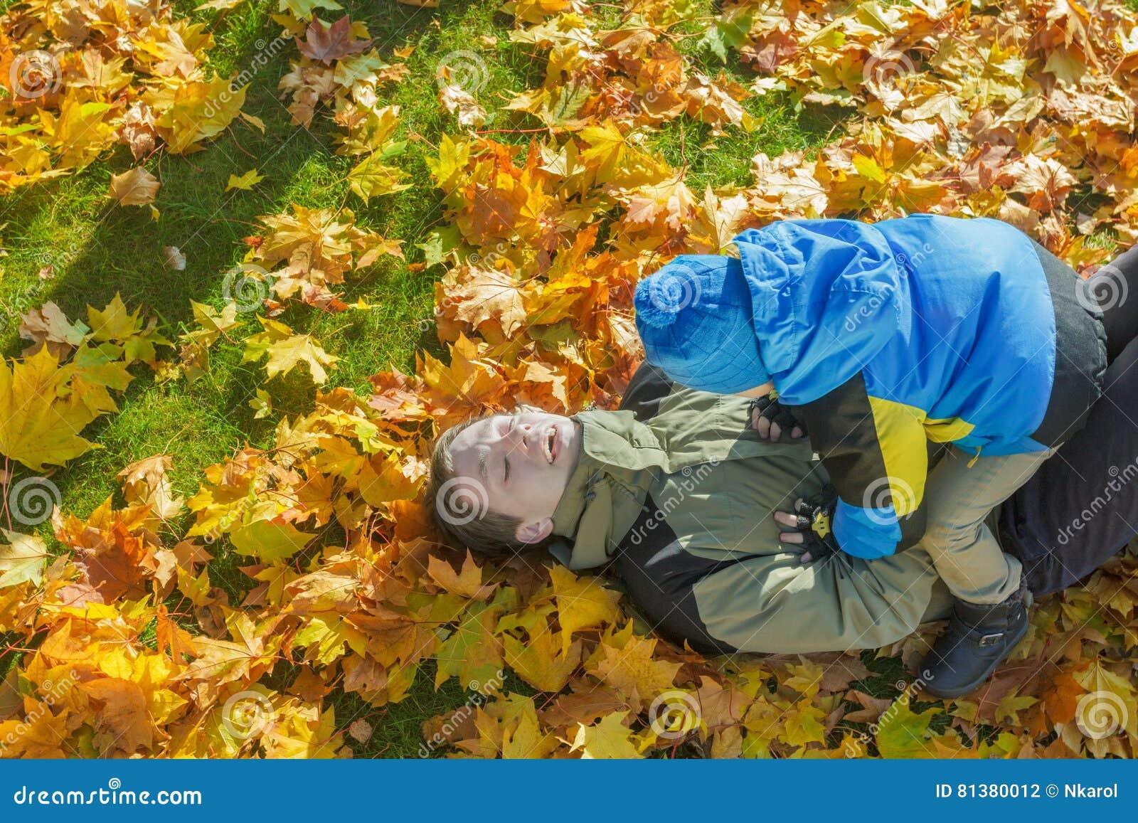 O retrato aéreo da luta brincalhão da família do pai e do filho no outono amarelo e alaranjado caído sae do groundcover