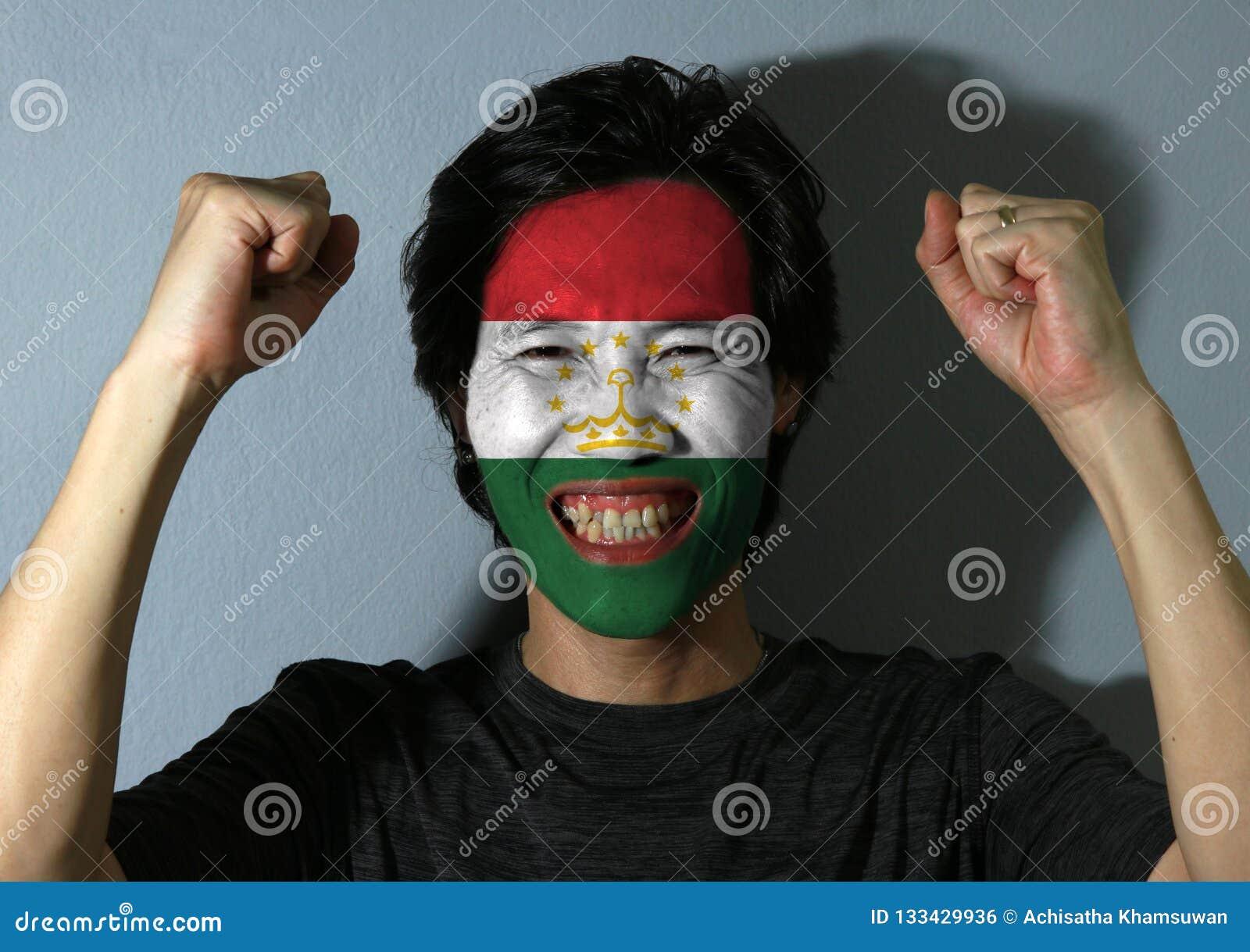 O retrato alegre de um homem com a bandeira de Tajiquistão pintou em sua cara no fundo cinzento O conceito do esporte