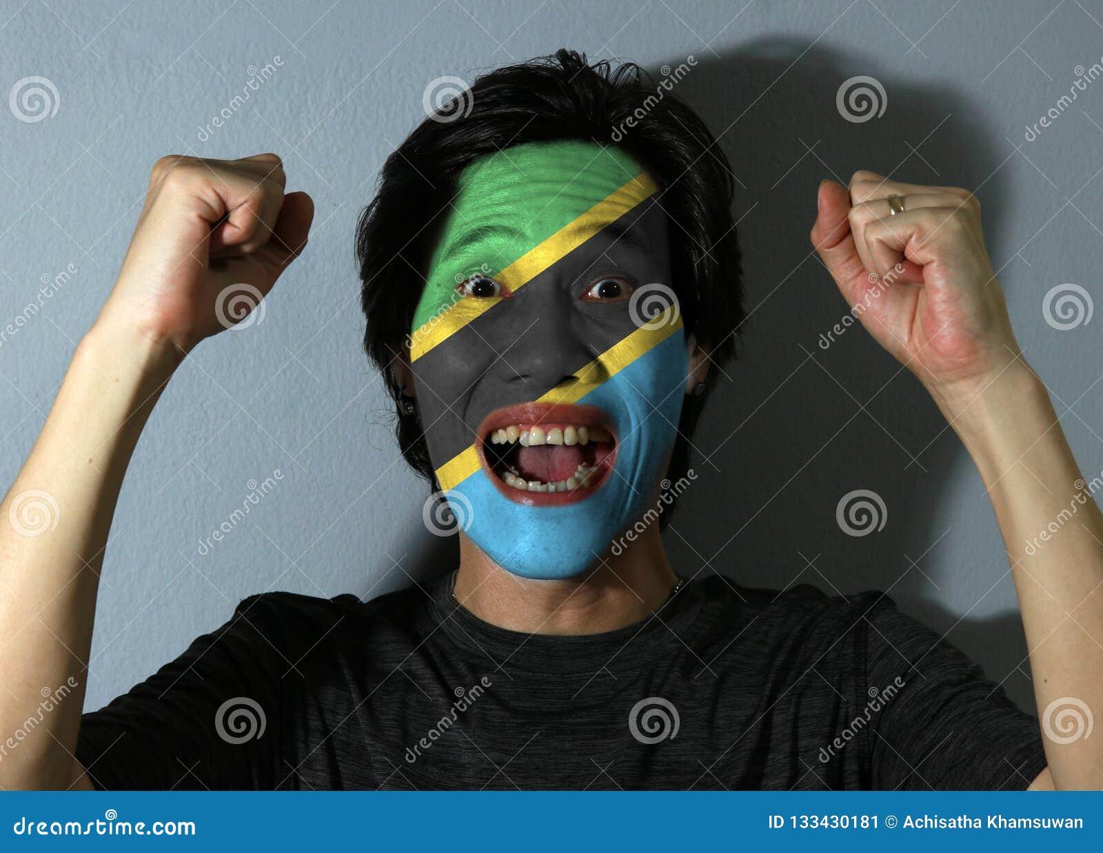 O retrato alegre de um homem com a bandeira de Tanzânia pintou em sua cara no fundo cinzento O conceito do esporte ou do nacional