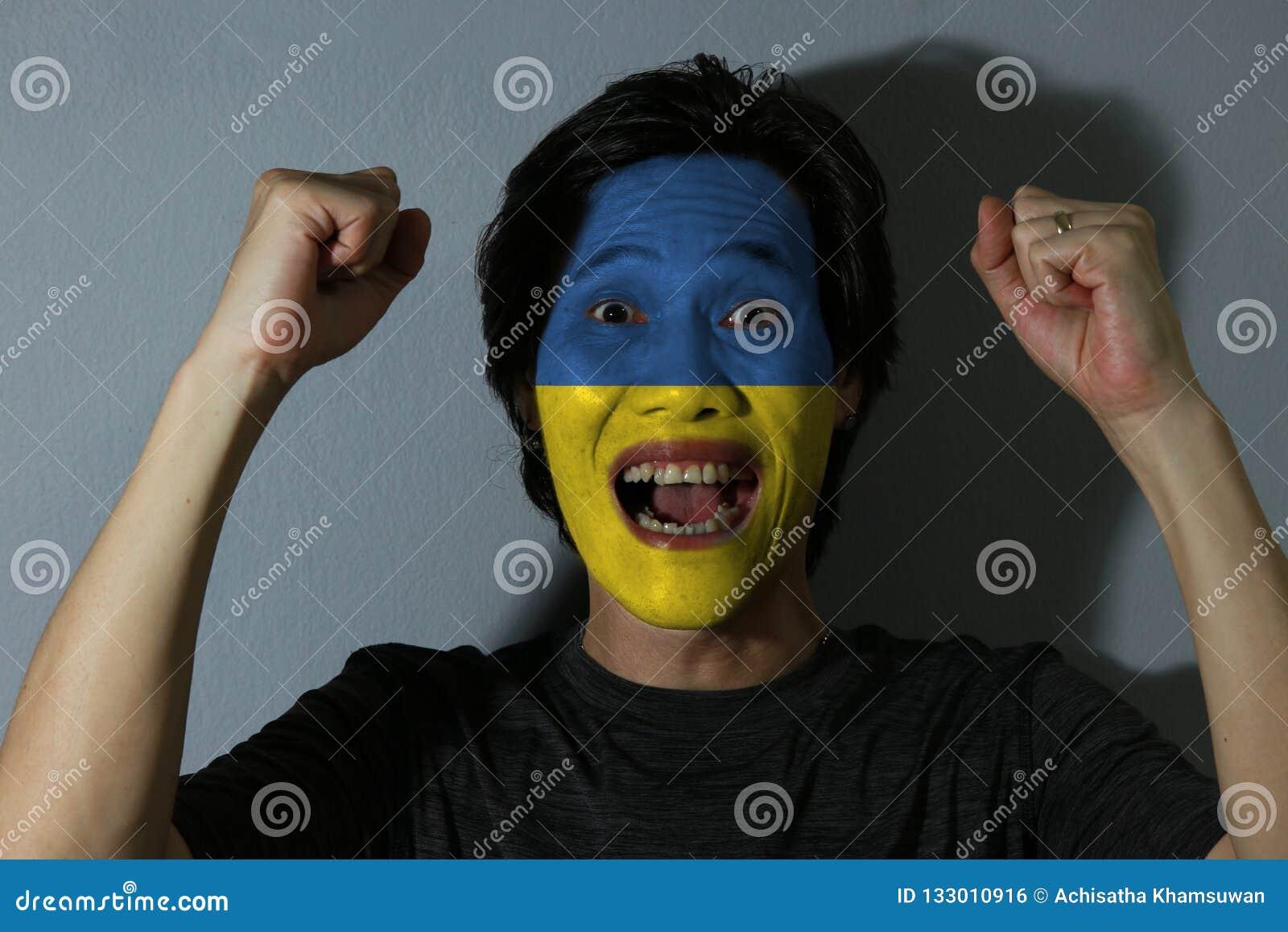 O retrato alegre de um homem com a bandeira de Ucrânia pintou em sua cara no fundo cinzento O conceito do esporte ou do nacionali