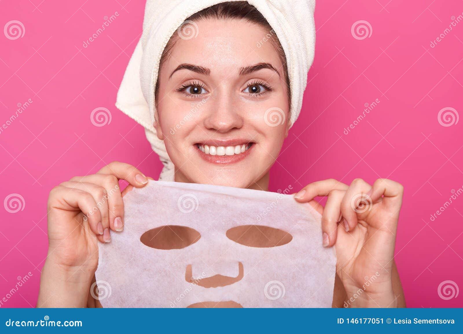 O retrato ascendente próximo da senhora bonita nova com a pele perfeita que põe a máscara protetora de nutrição, tempo aos proced