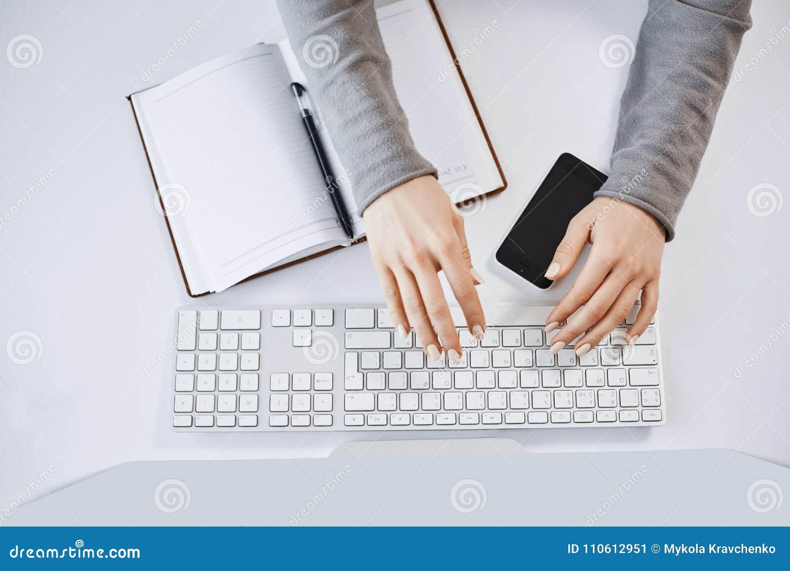 O retrato colhido da mulher entrega a datilografia no teclado e o trabalho com computador e dispositivos Freelancer fêmea moderno