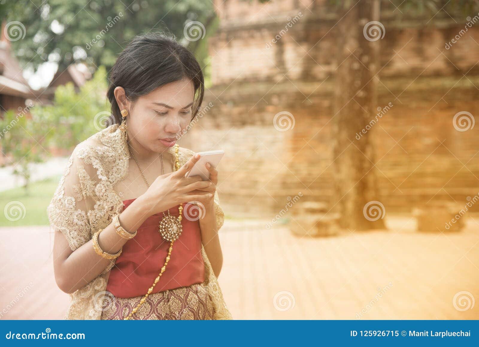 O retrato da fêmea asiática em vestidos tradicionais levanta o móbil do uso