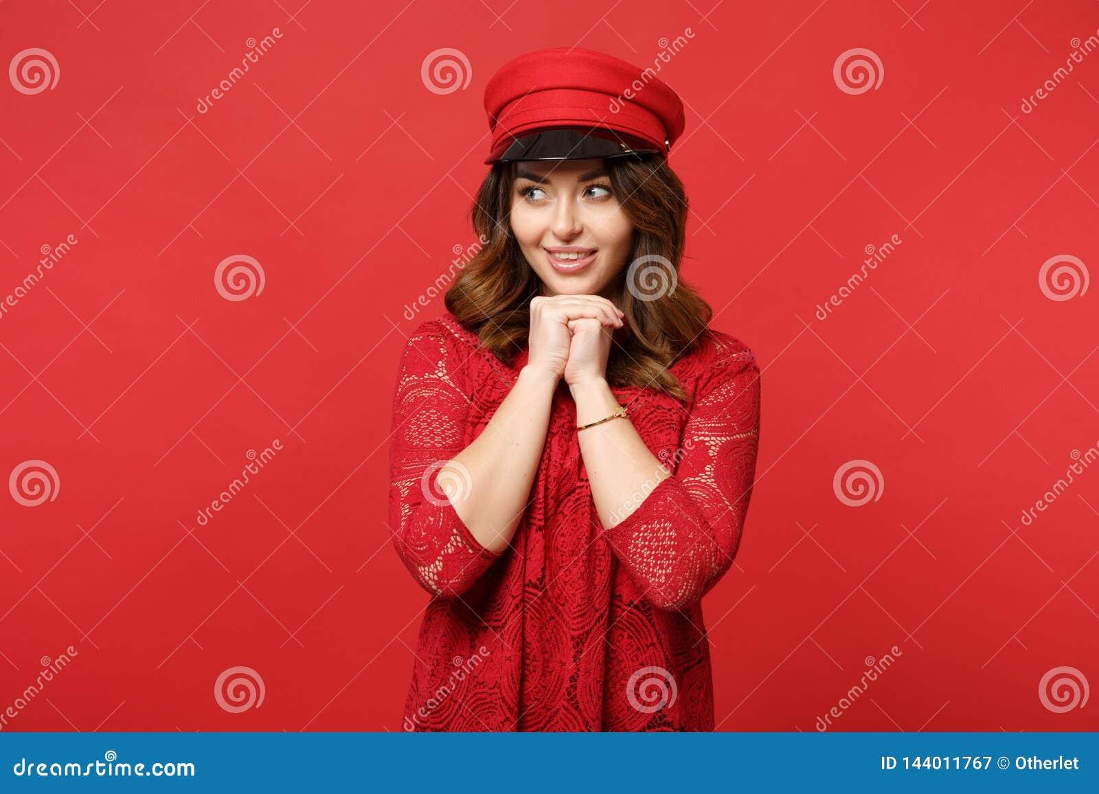 O retrato da jovem mulher atrativa no vestido e no tampão do laço que olham de lado, colocou o suporte da mão sobre o queixo isol