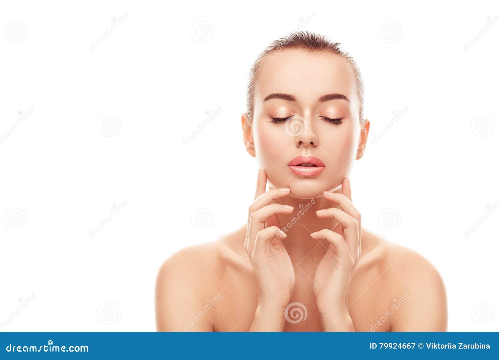 O retrato da jovem mulher bonita com pele limpa, fresca toca em sua cara no fundo branco isolado