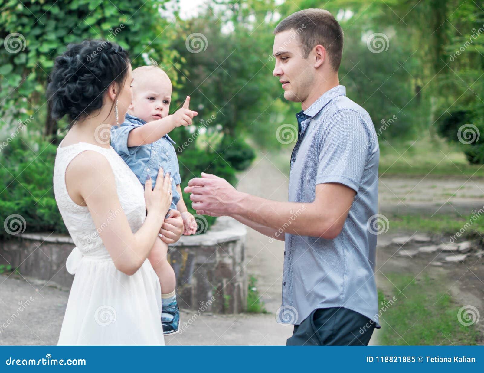 O retrato da mãe bonita da família nova que guarda o bebê pequeno do filho e o pai no verão verde estacionam Rapaz pequeno no cas