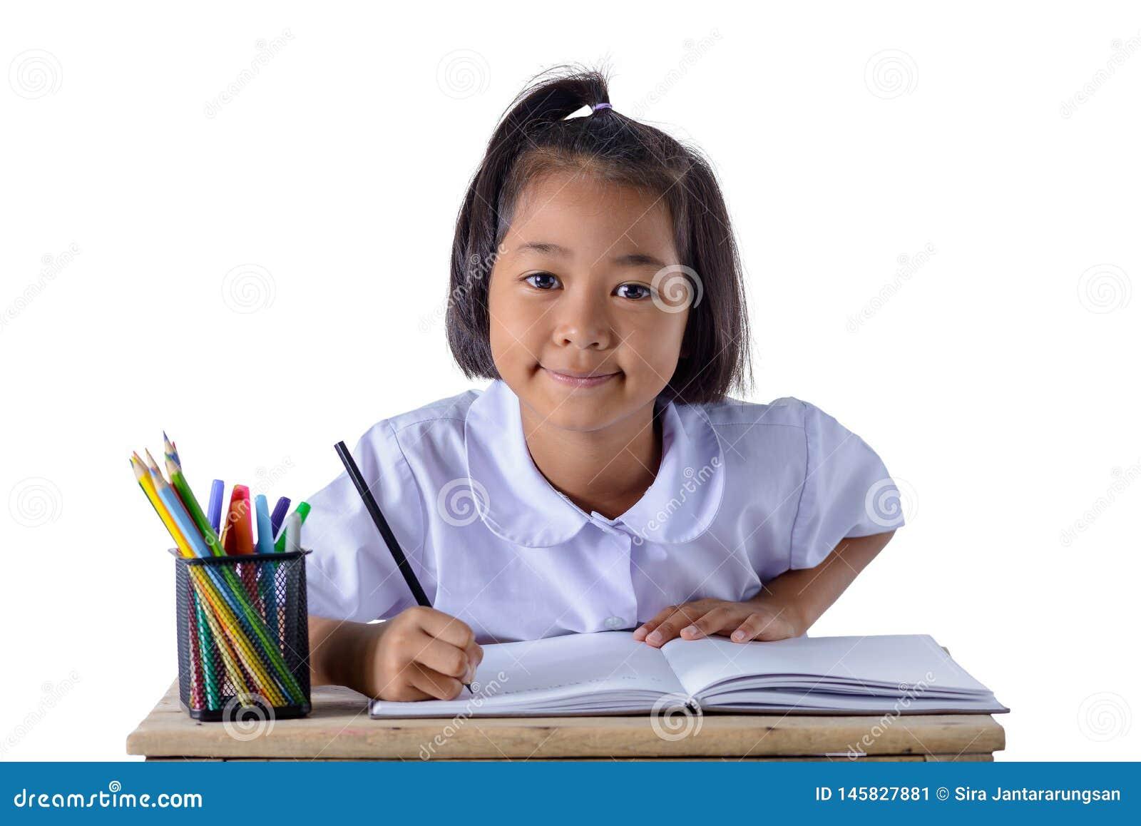 O retrato da menina asi?tica na farda da escola est? tirando com os l?pis da cor isolados no fundo branco