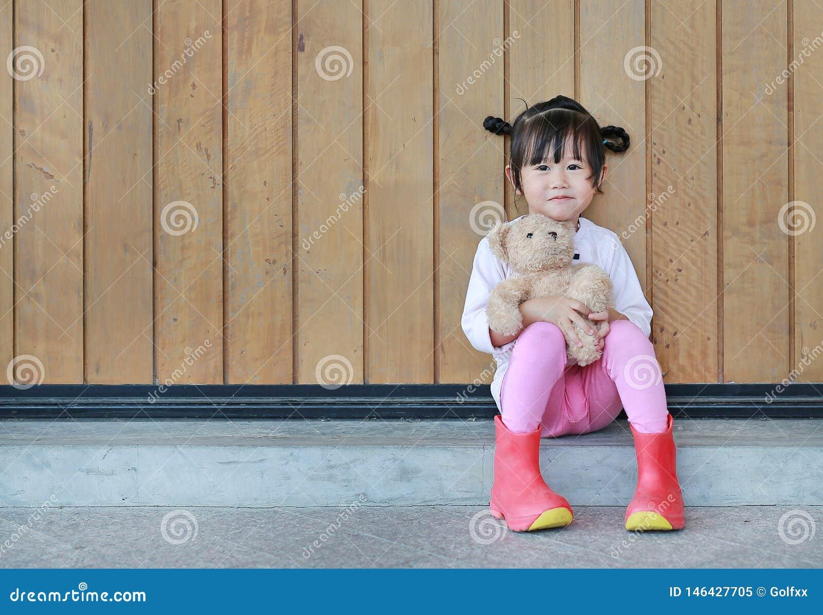 O retrato da menina bonito senta-se e abra?ando Teddy Bear contra a parede de madeira da prancha