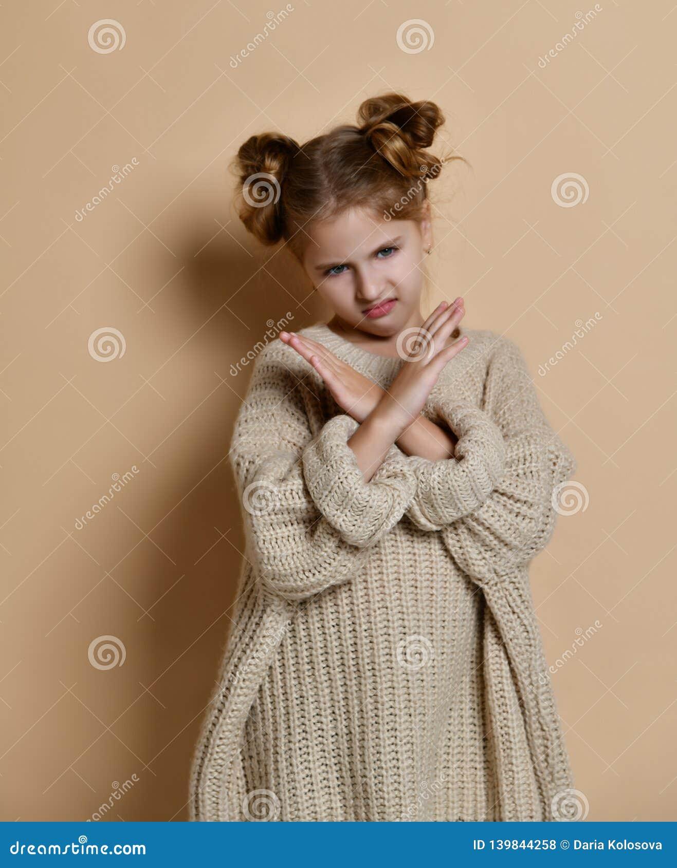 O retrato da menina séria, infeliz da criança que guarda dois braços cruzou-se, não gesticulando nenhum sinal, olhando afastado a