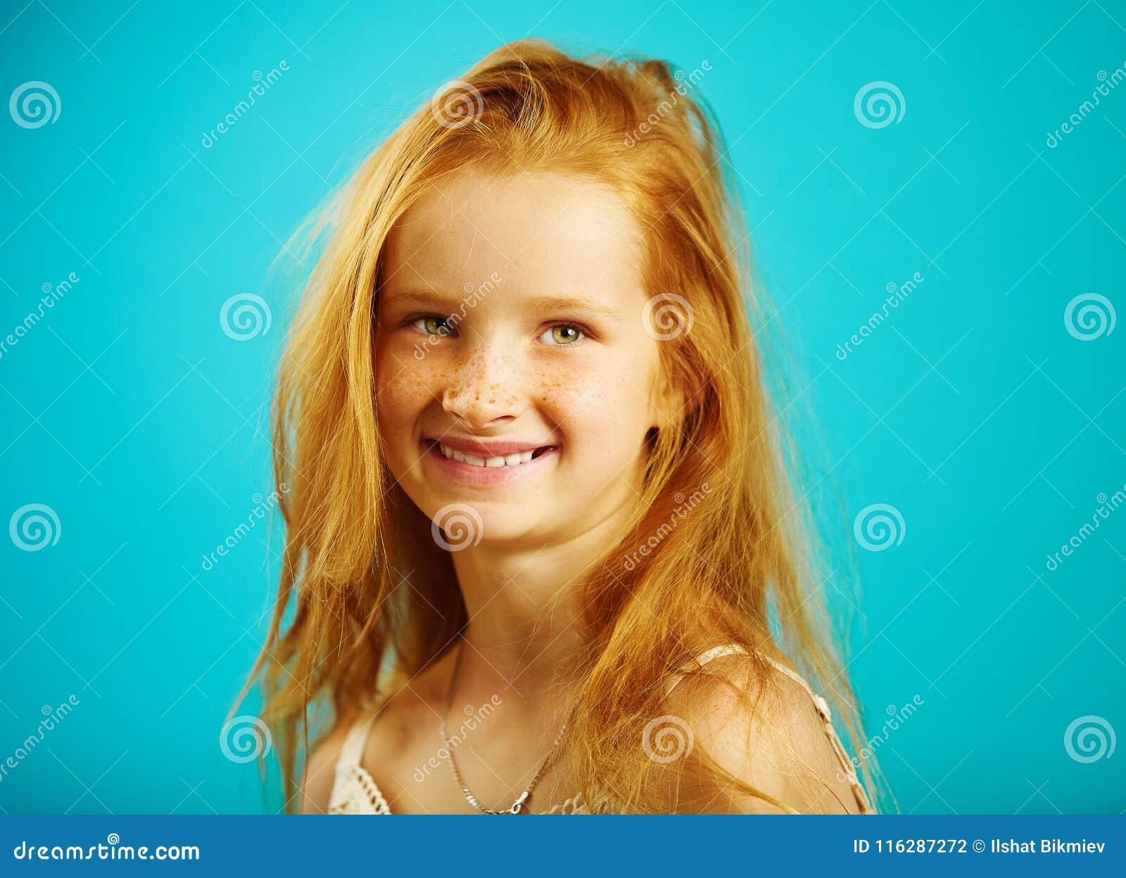 O retrato da menina sete anos velha com cabelo vermelho impetuoso, sardas bonitos, sorrindo sinceramente, expressa a confiança e