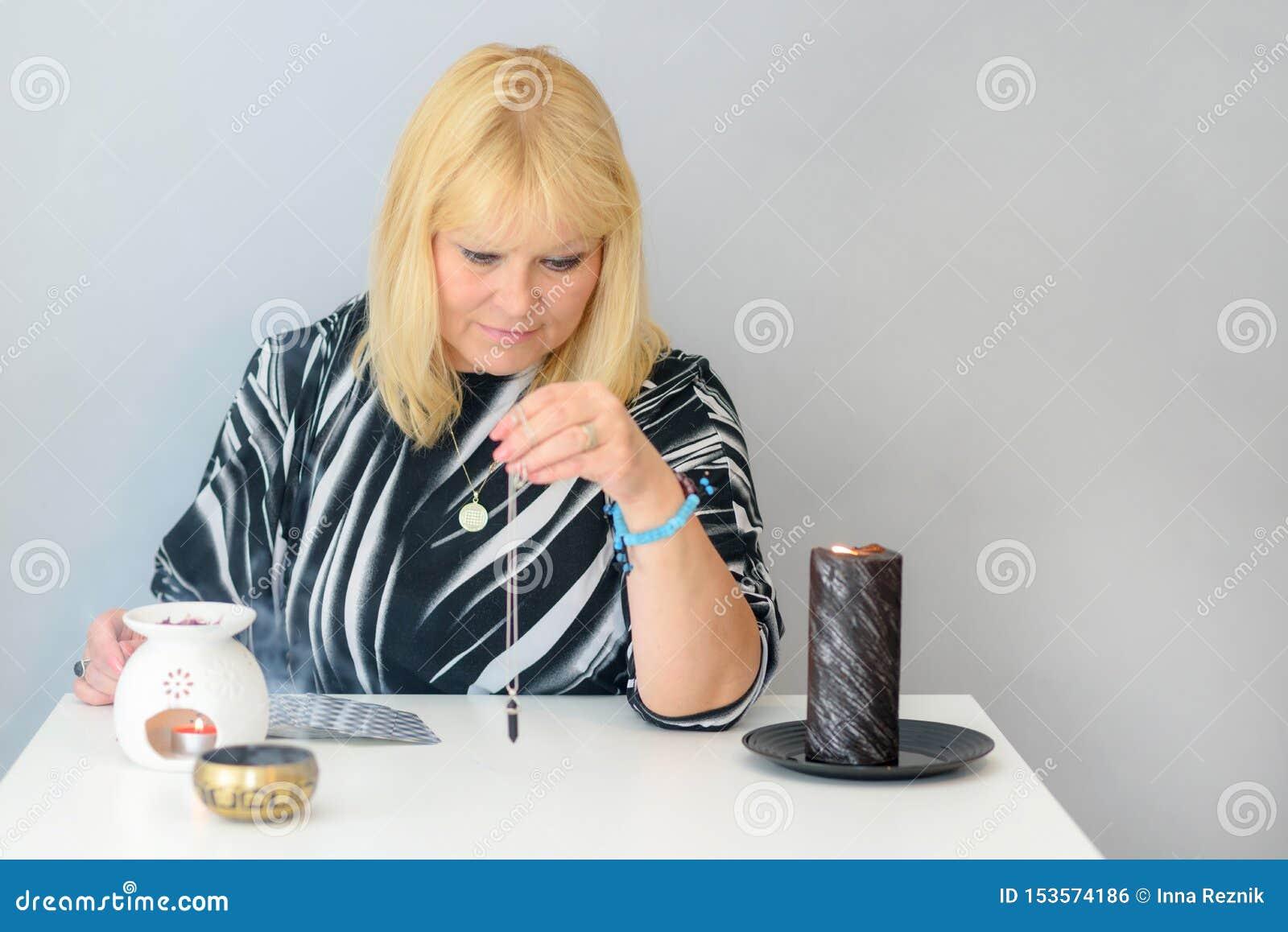 O retrato da mulher bonita da Idade Média senta-se perto de uma mesa do caixa de fortuna com os cartões de tarô, o pêndulo preto