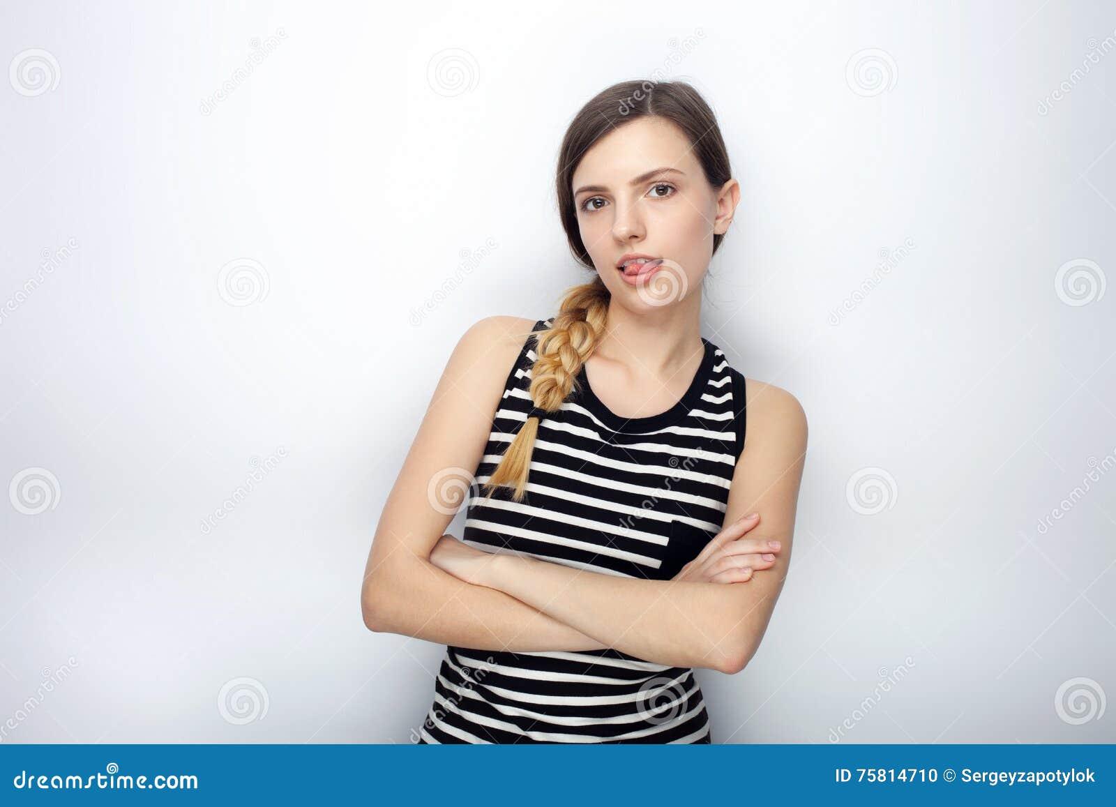 O retrato da mulher bonita nova impertinente em camisa listrada cruzou as mãos que mostram a língua que levanta para os testes mo