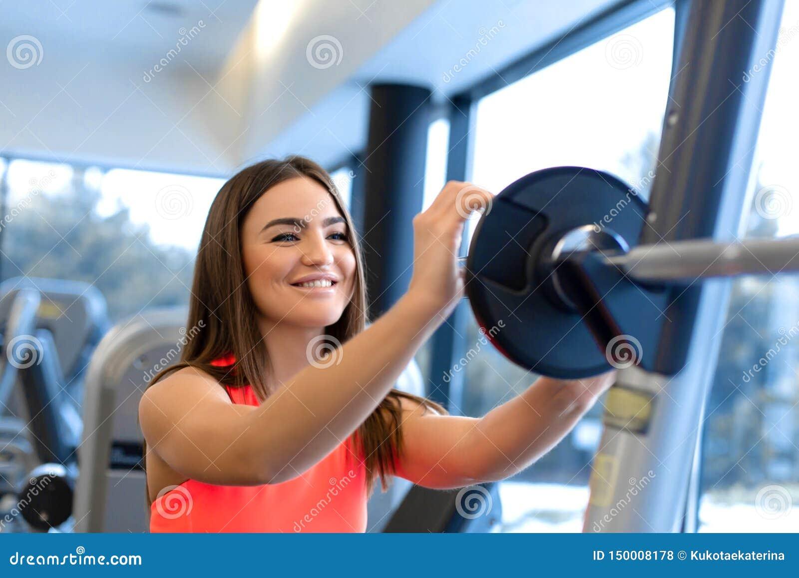 O retrato da mulher consider?vel p?e a placa do peso sobre o barbell no gym