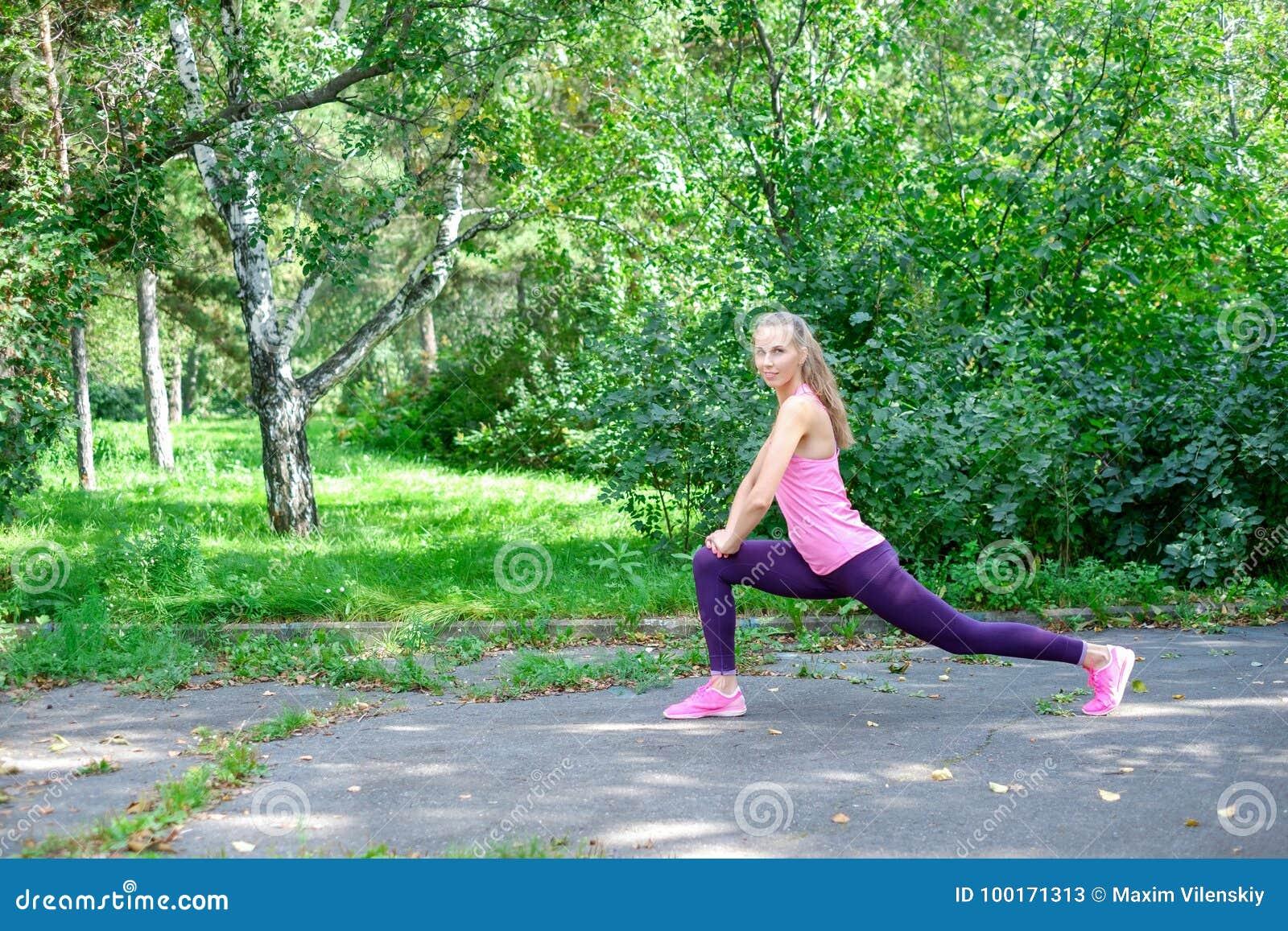 O retrato da mulher desportiva que faz o esticão exercita no parque antes de treinar Atleta fêmea que prepara-se para movimentar-