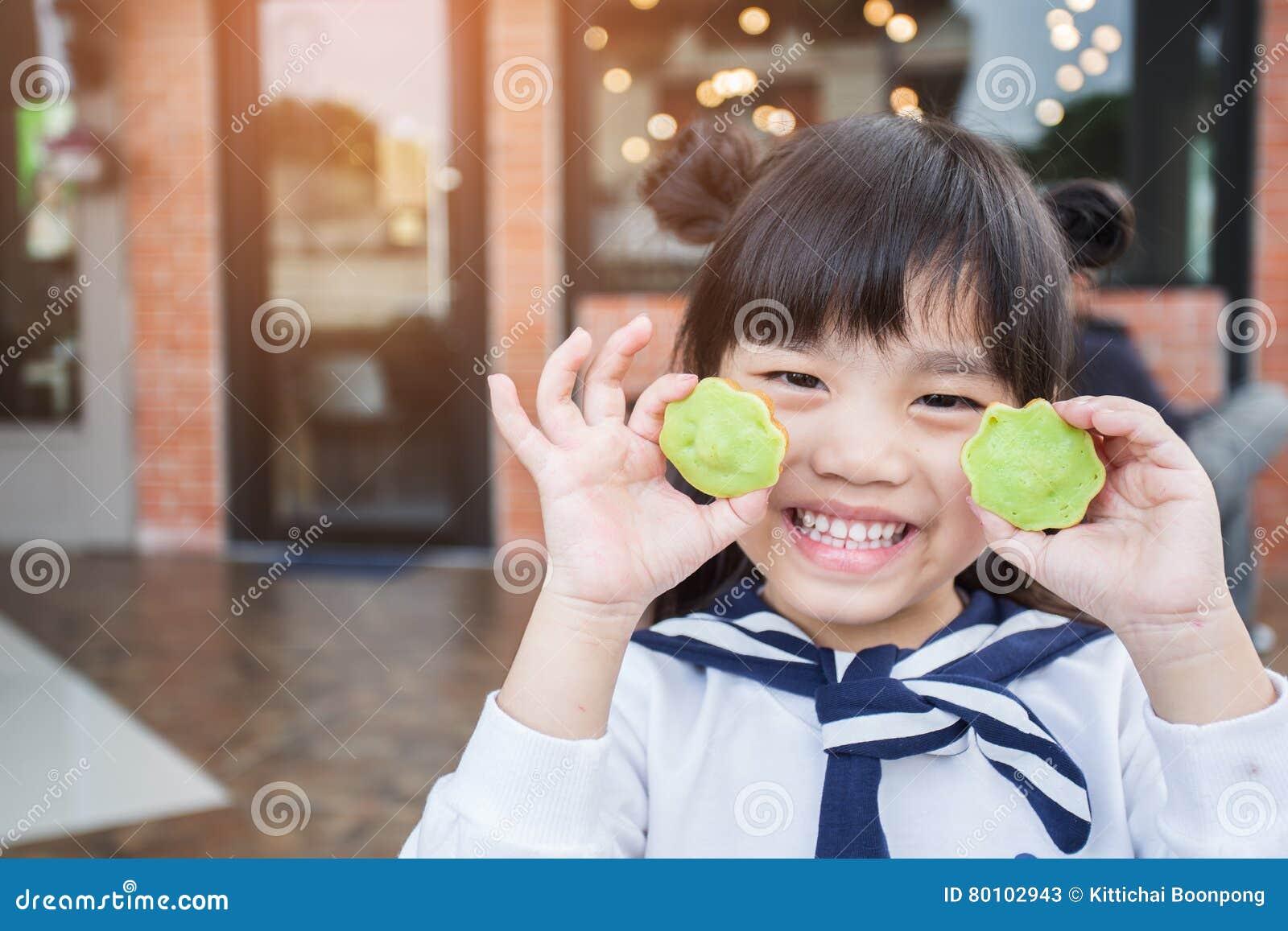 O retrato de crianças bonitas de Ásia sente feliz comendo duas galdérias da sobremesa