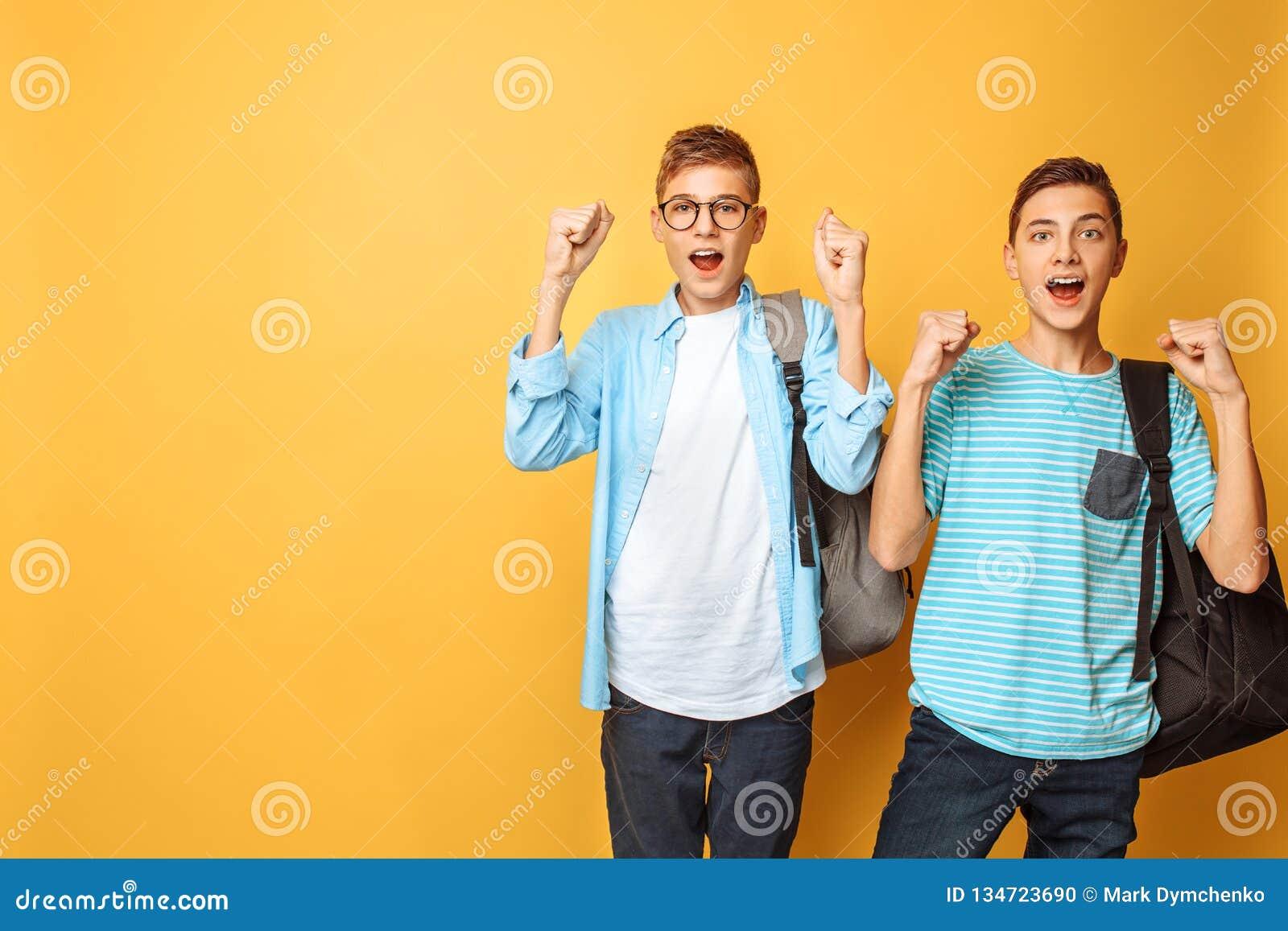 O retrato de dois adolescentes chocados, indivíduos mostra o gesto da vitória, no fundo amarelo