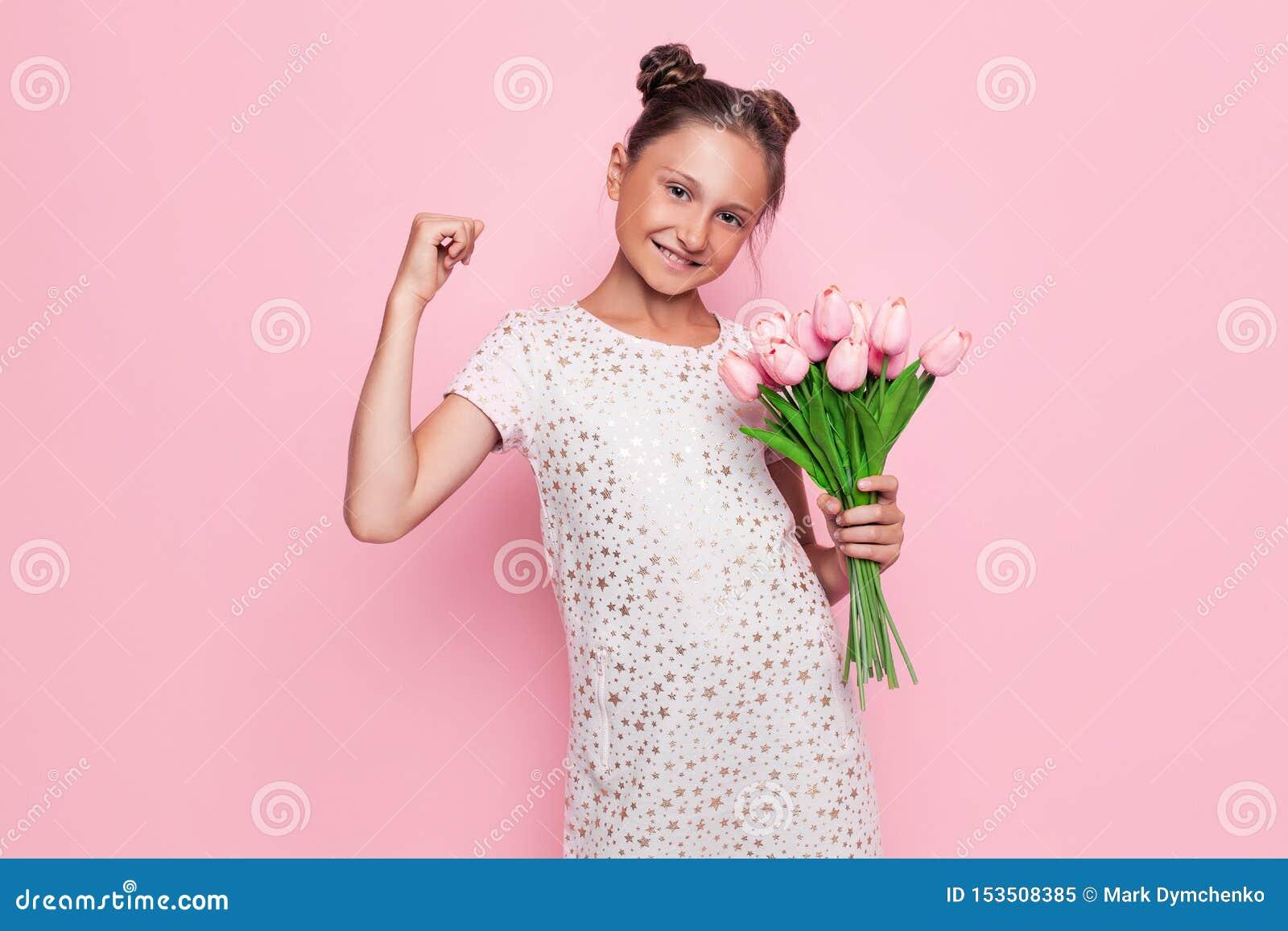 O retrato de um adolescente bonito em um vestido à moda com um ramalhete das flores, mostra um gesto da vitória e do sucesso