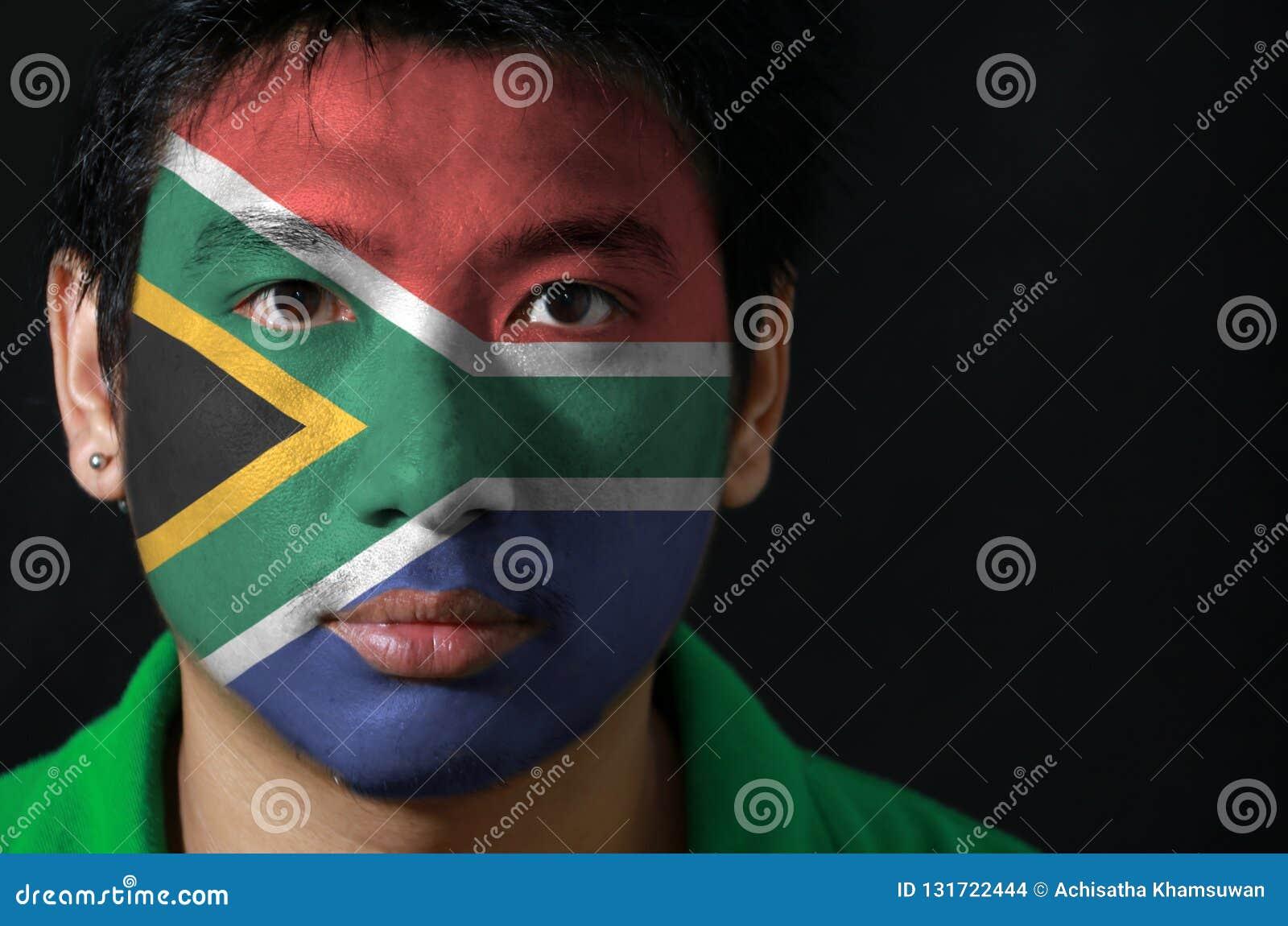 O retrato de um homem com a bandeira da África do Sul pintou em sua cara no fundo preto