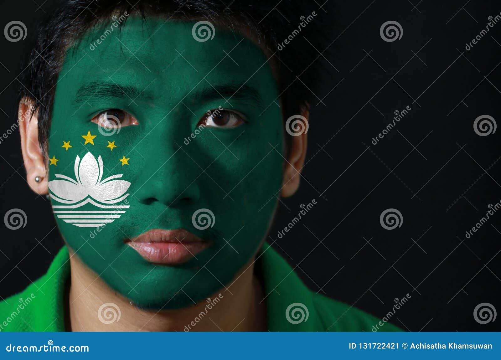 O retrato de um homem com a bandeira do Macau pintou em sua cara no fundo preto