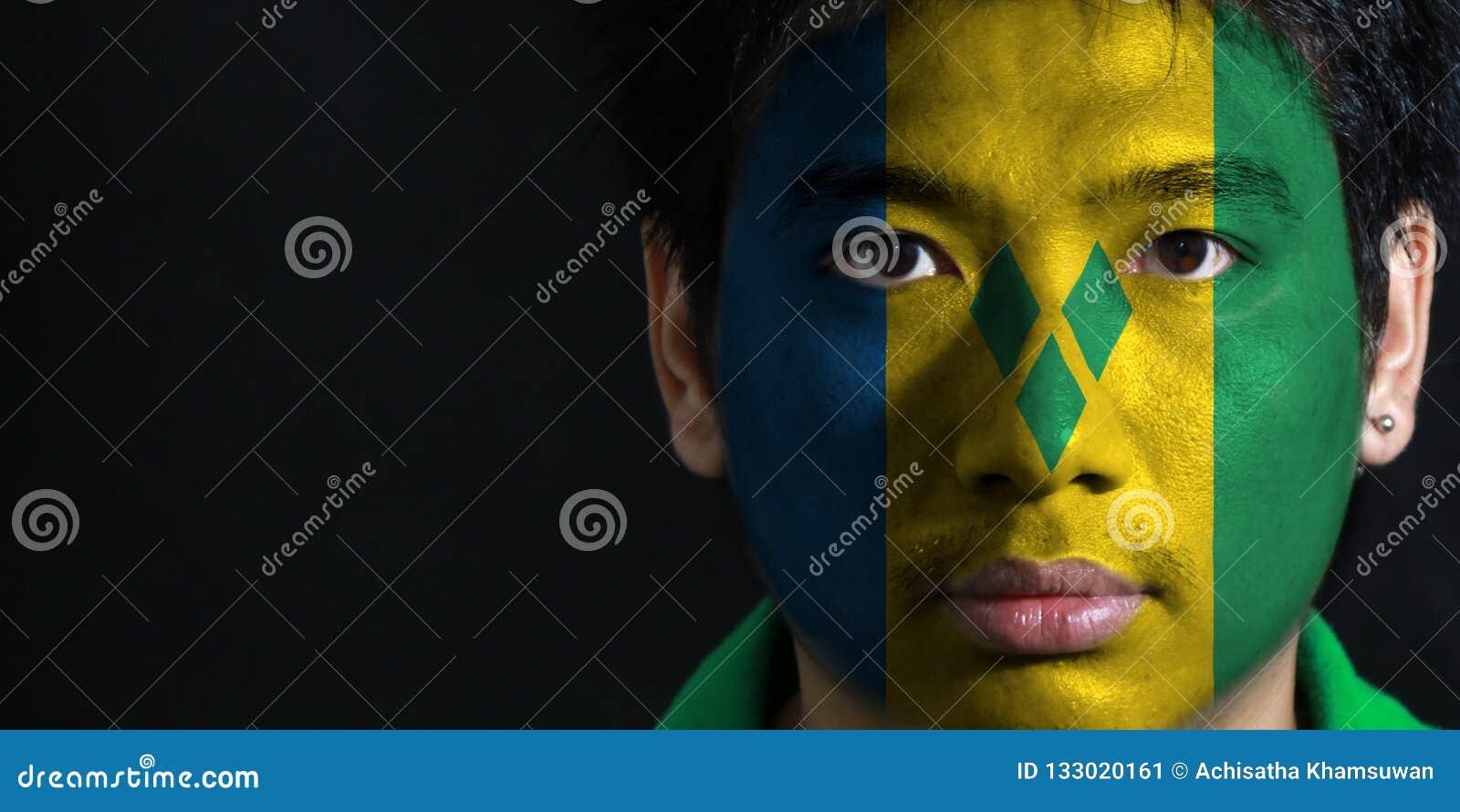 O retrato de um homem com a bandeira do Saint Vincent pintou em sua cara no fundo preto