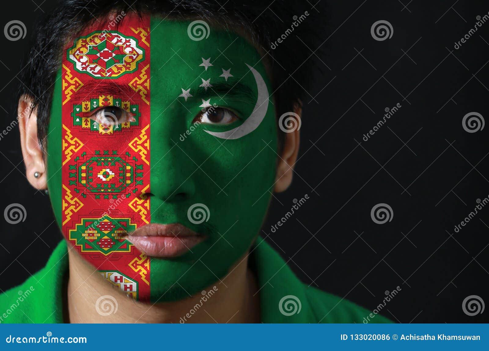 O retrato de um homem com a bandeira de Turquemenistão pintou em sua cara no fundo preto