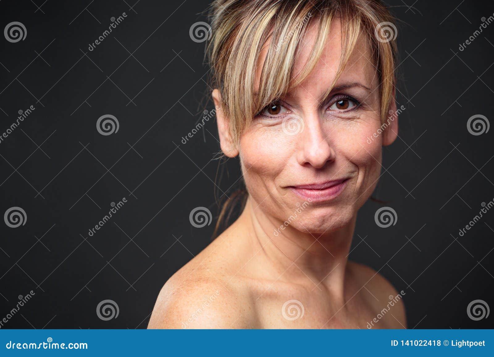 O retrato de um meio de sorriso envelheceu a mulher caucasiano contra o fundo escuro