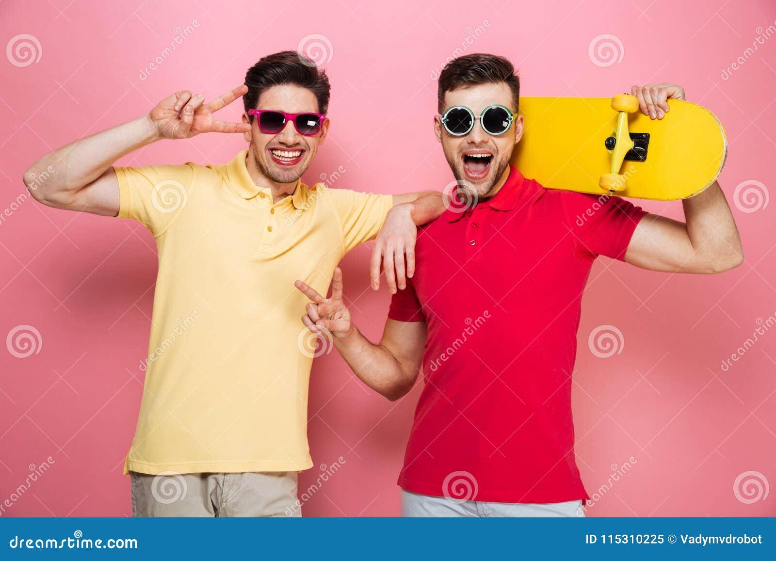 O retrato de um par masculino alegre fresco que mostra a paz gesticula