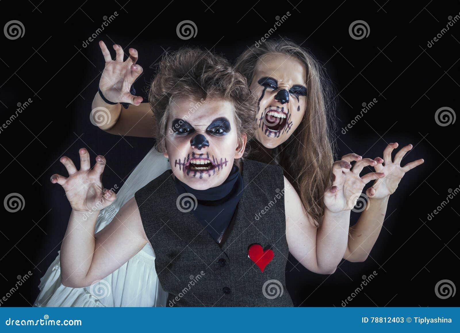 O retrato de uma menina e de um menino vestiu-se para a celebração do Dia das Bruxas