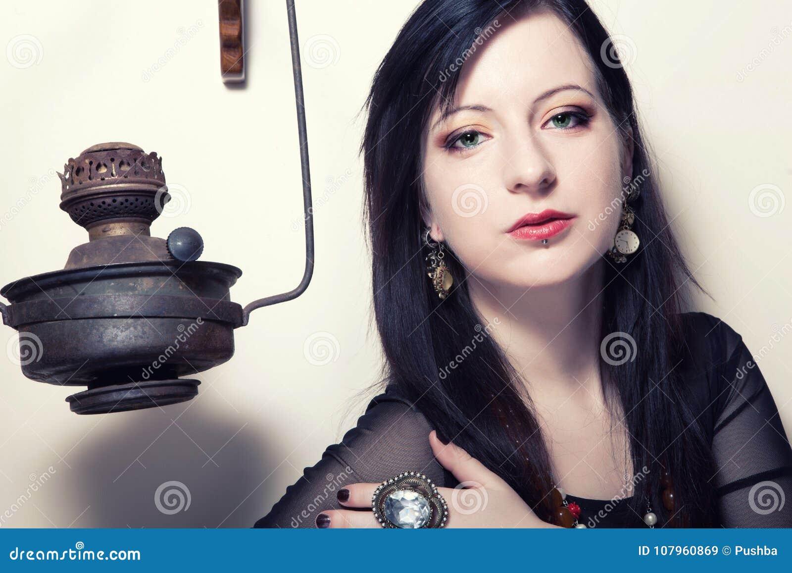 O retrato de uma menina polonesa bonita nova com olhos verdes vestiu-se em um espartilho na perspectiva de um moedor de café do v
