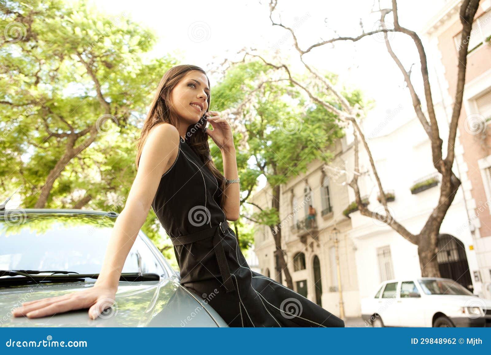 Mulher de negócios que inclina-se no carro com telefone.