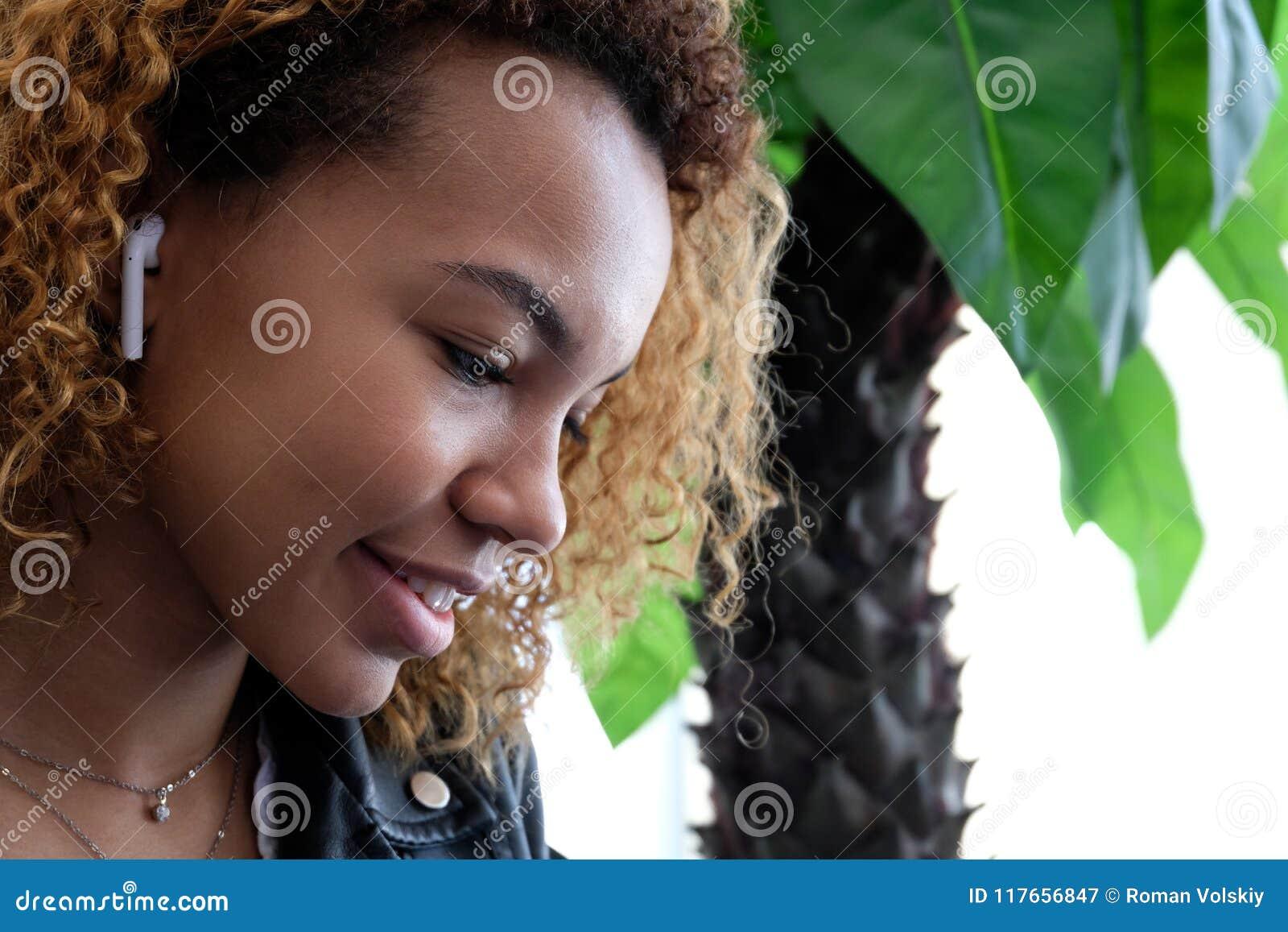 O retrato de uma mulher negra moderna nova bonita, em um casaco de cabedal com airpods em sua orelha, escuta a música africano