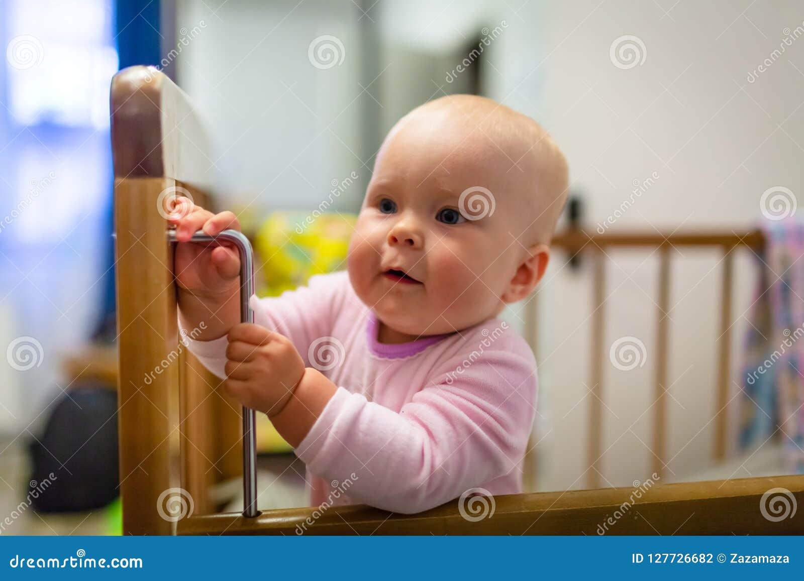 O retrato do bebê bonito com olhos azuis está estando na ucha O infante adorável está levantando-se e sorrir Conceito