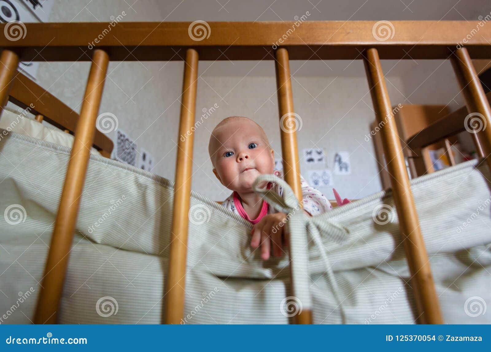 O retrato do bebê bonito com olhos azuis está sentando-se na ucha O infante adorável senta-se apenas no berço e é interessado