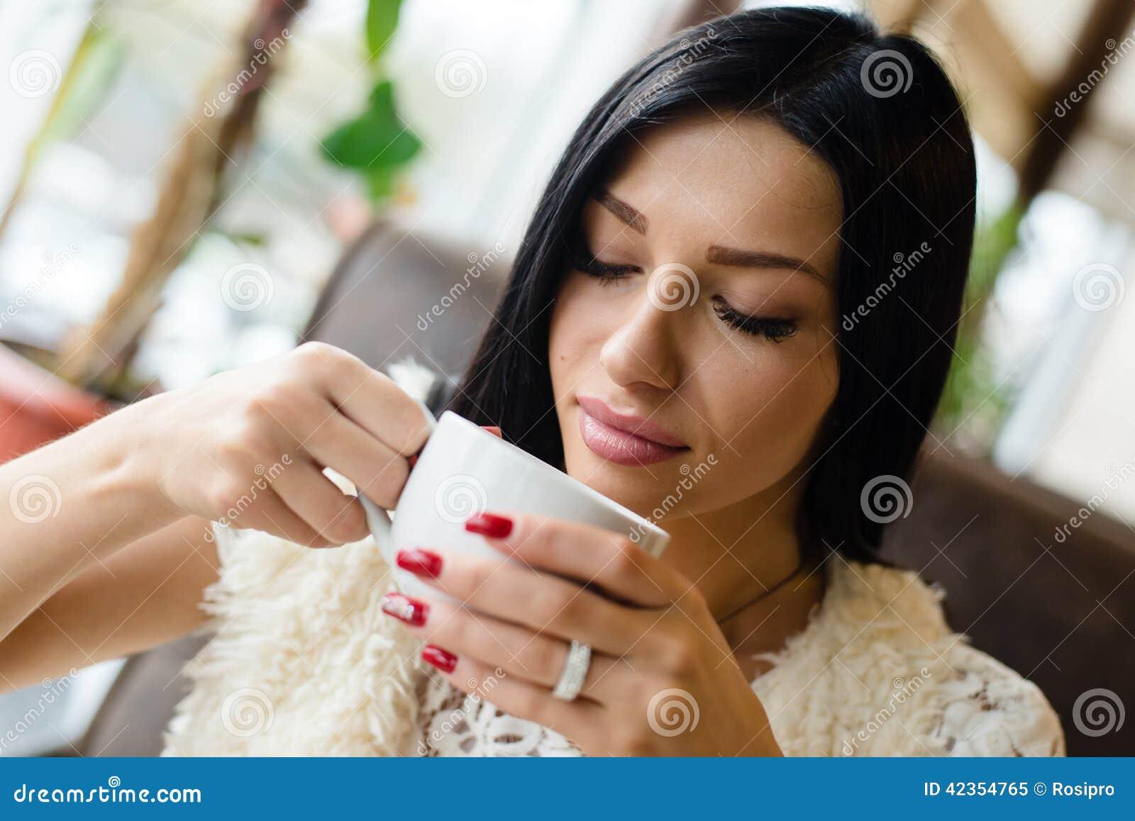 O retrato do close up da jovem mulher moreno  sexy  bonita bebendo da menina do café ou do chá que tem o divertimento que sorri d