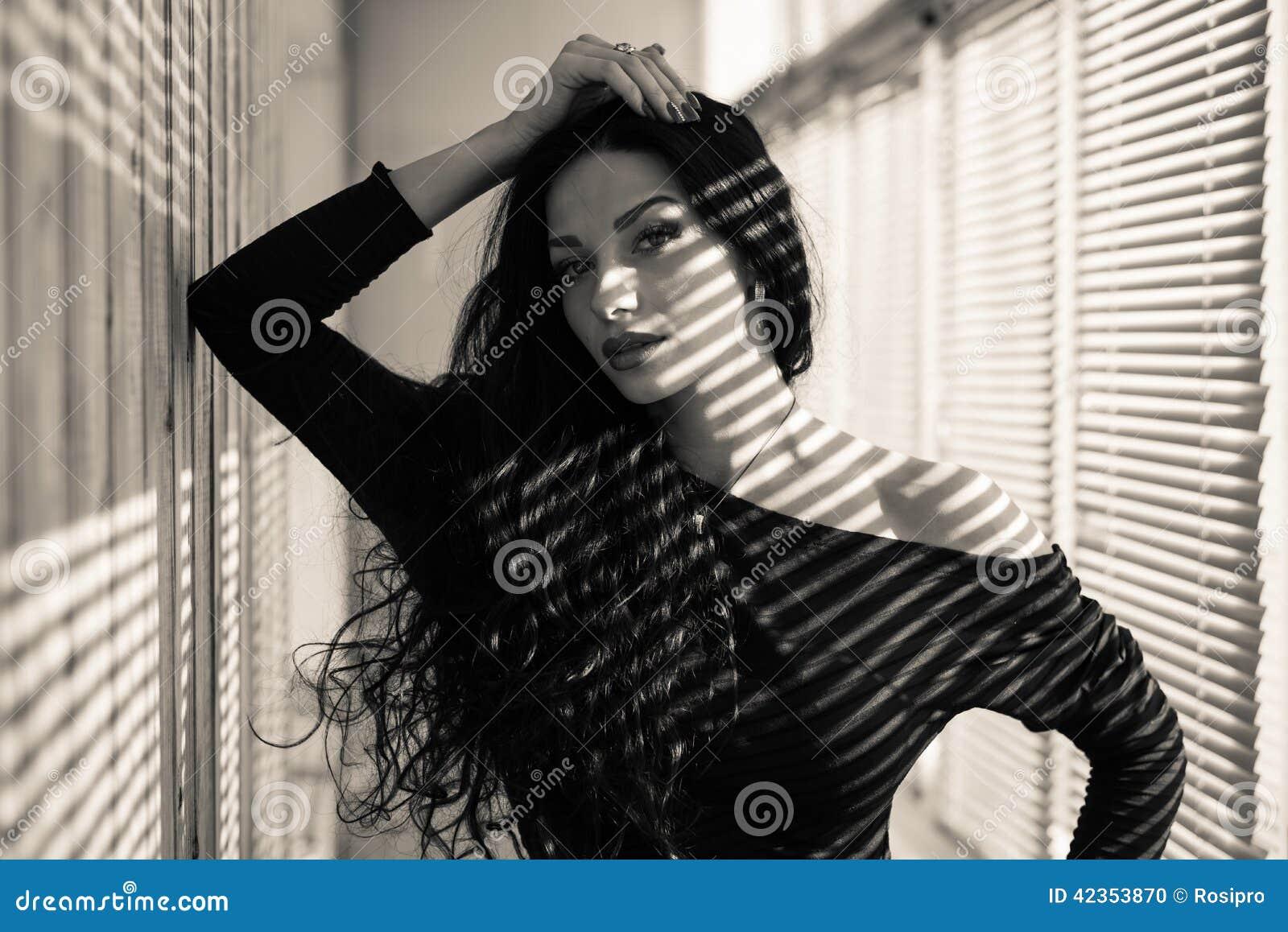 O retrato do close up da menina moreno  sexy  bonita que tem o divertimento que olha sensualmente a câmera no sol iluminado cega
