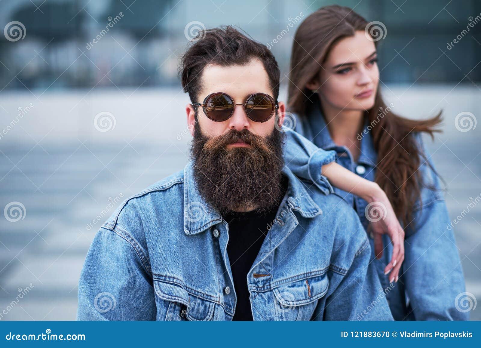 O retrato do close-up de um par do moderno de um homem farpado brutal nos óculos de sol e na sua amiga vestiu-se em revestimentos