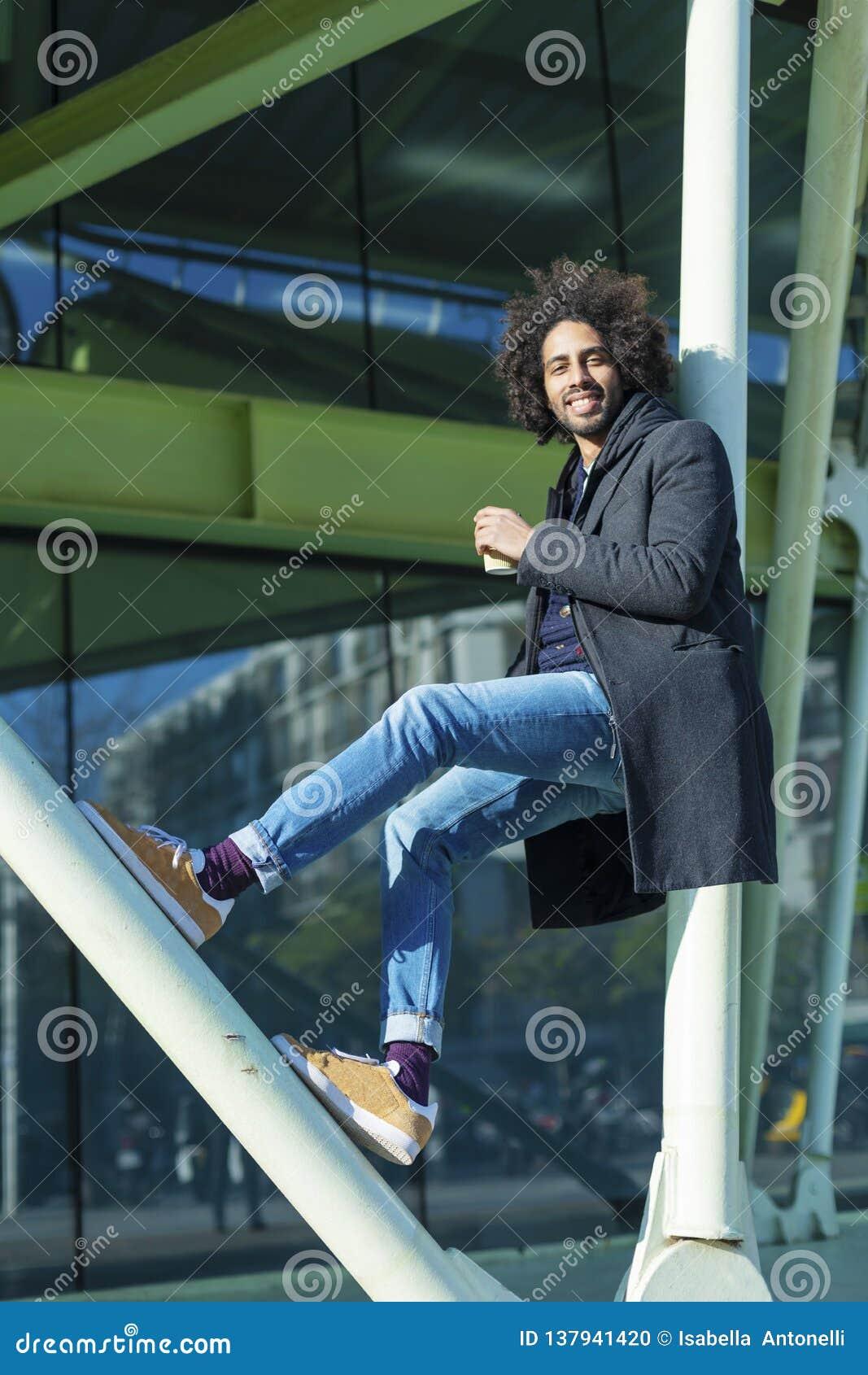 O retrato do homem afro considerável alegre no vestuário desportivo que levanta para guardar farpado do homem novo da câmera leva