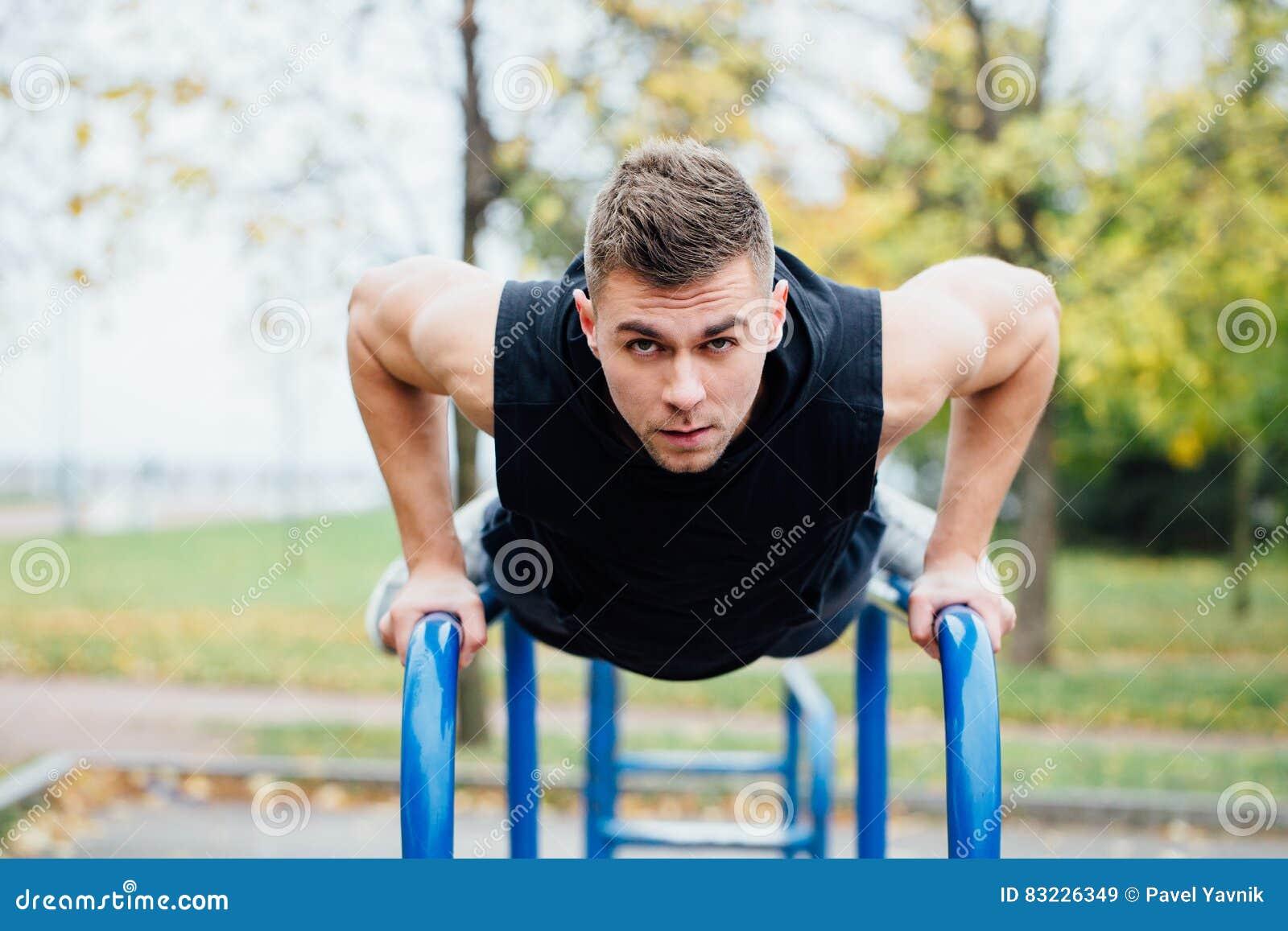 O retrato do homem novo muscular focalizado no exercício preto veste fazer mergulhos em barras paralelas