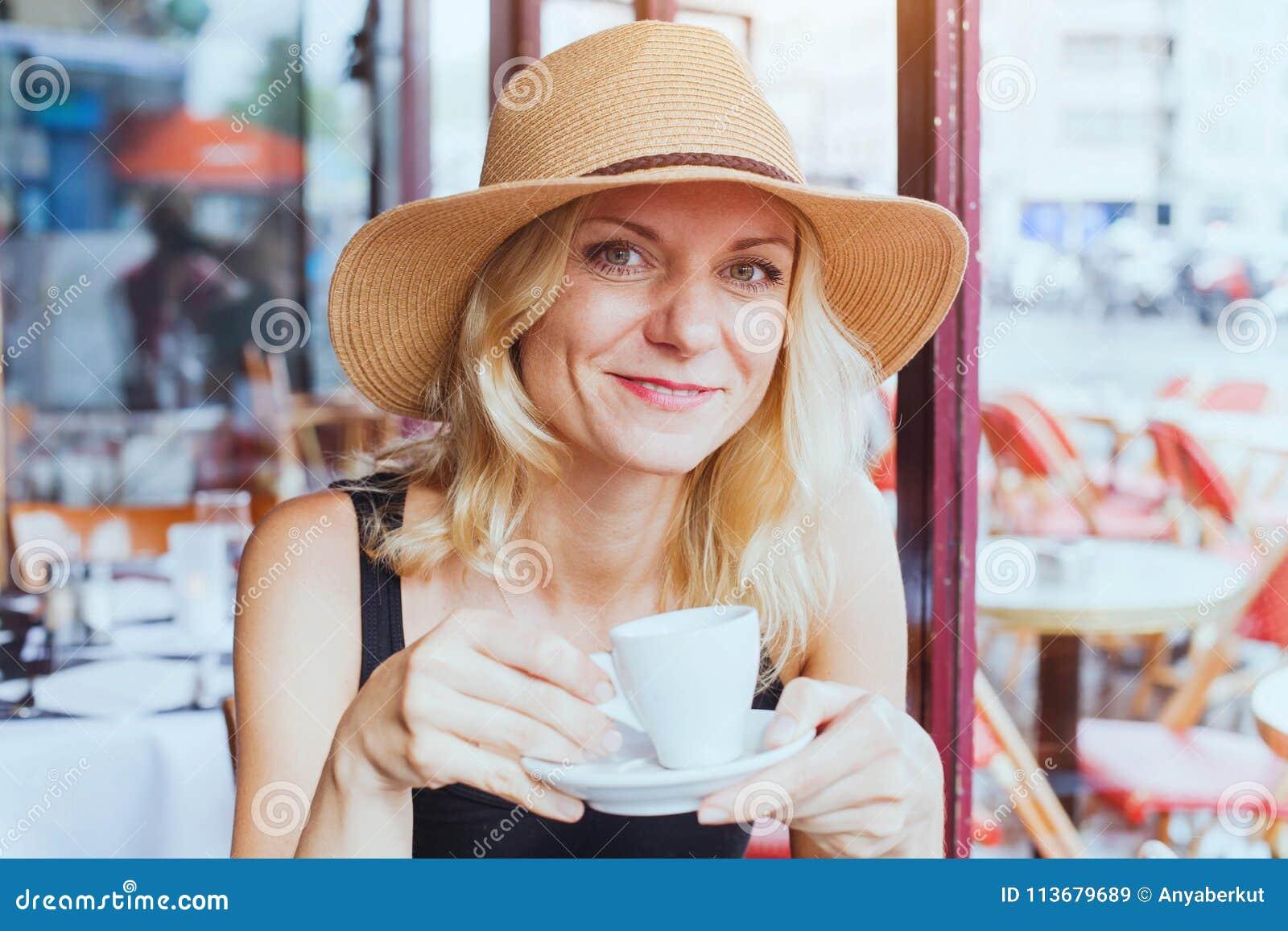 O retrato do meio bonito da forma envelheceu a mulher no café com xícara de café, sorriso feliz