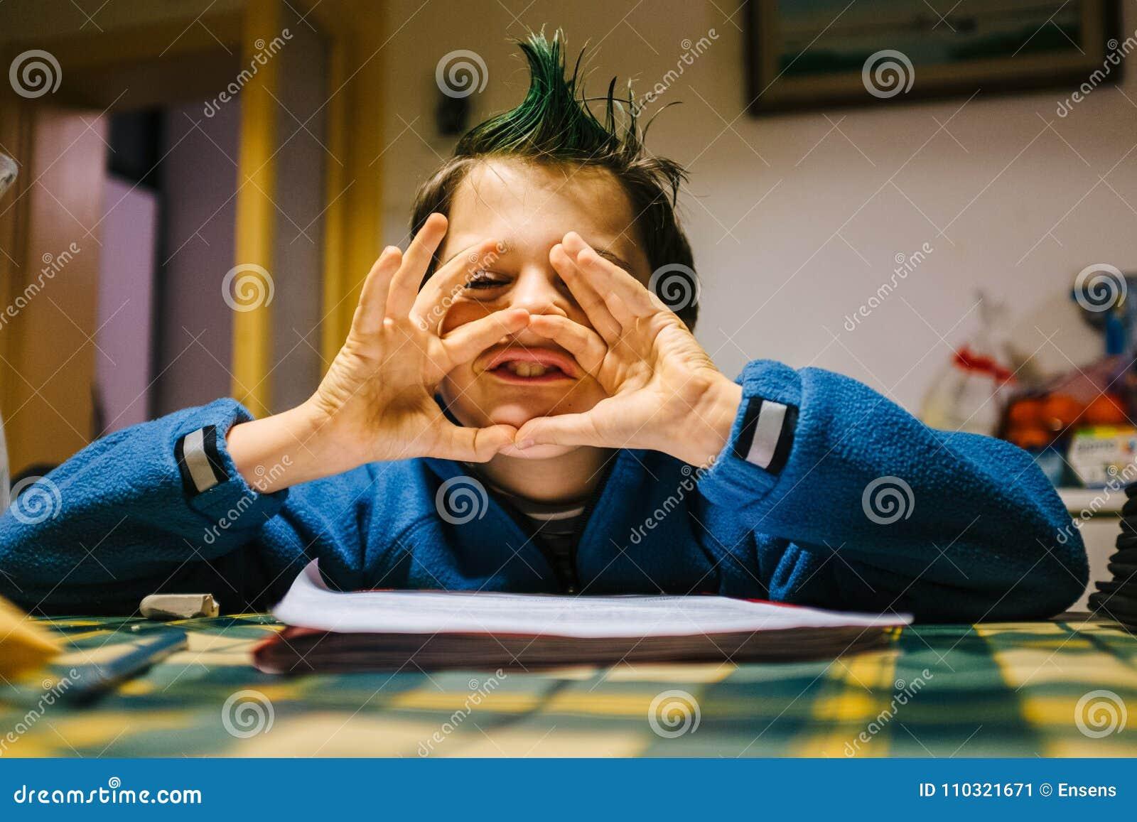 O retrato do menino da criança de 9 anos em casa com crista do verde coloriu h
