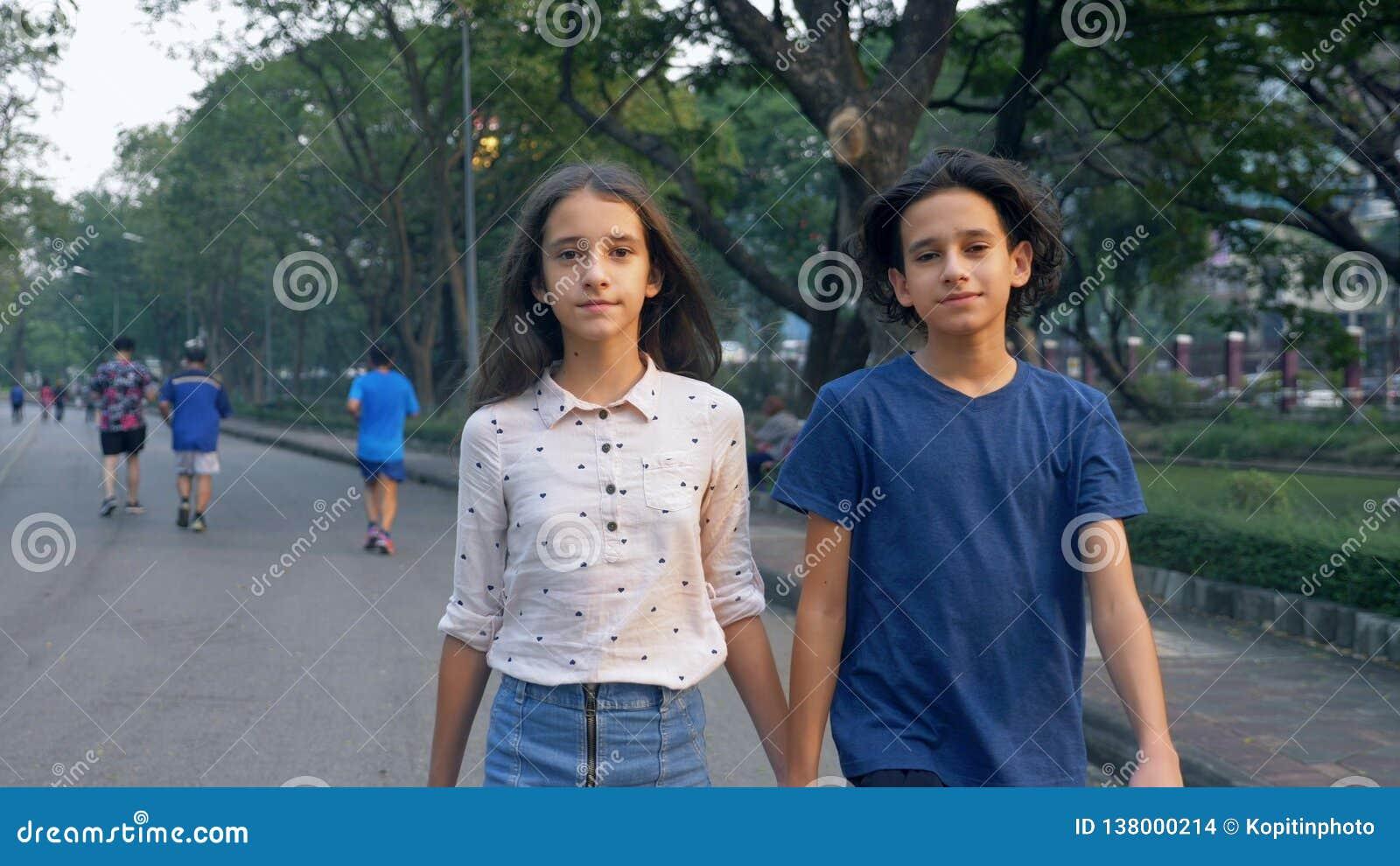 O retrato dos adolescentes, o menino e a menina que andam na natureza em um parque grande com os gêmeos do prazer, do irmão e da