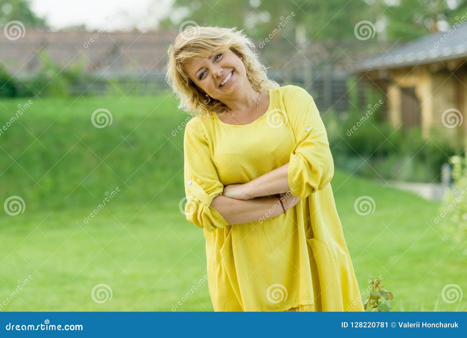 O retrato exterior da mulher de meia idade madura positiva, fêmea com braços cruzou-se, sorriso bonito, jardim do fundo